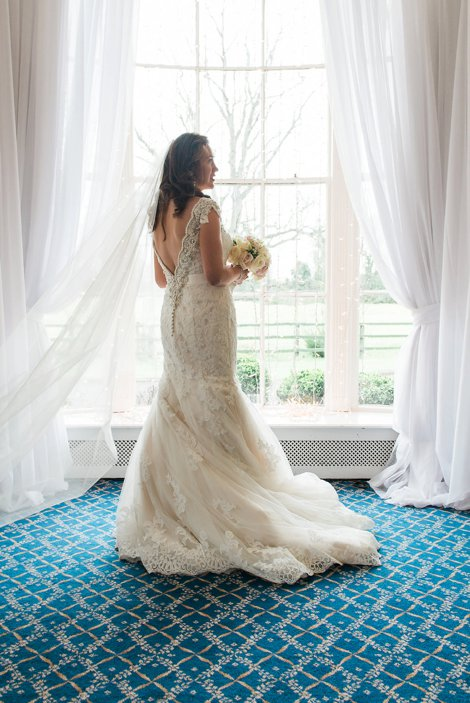 Bride standing in front of a window in wedding dress