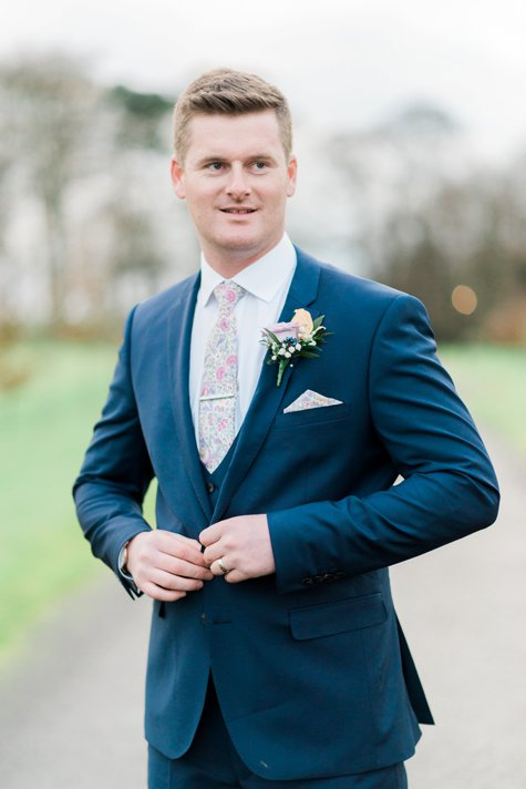 Groom buttoning navy suit jacket