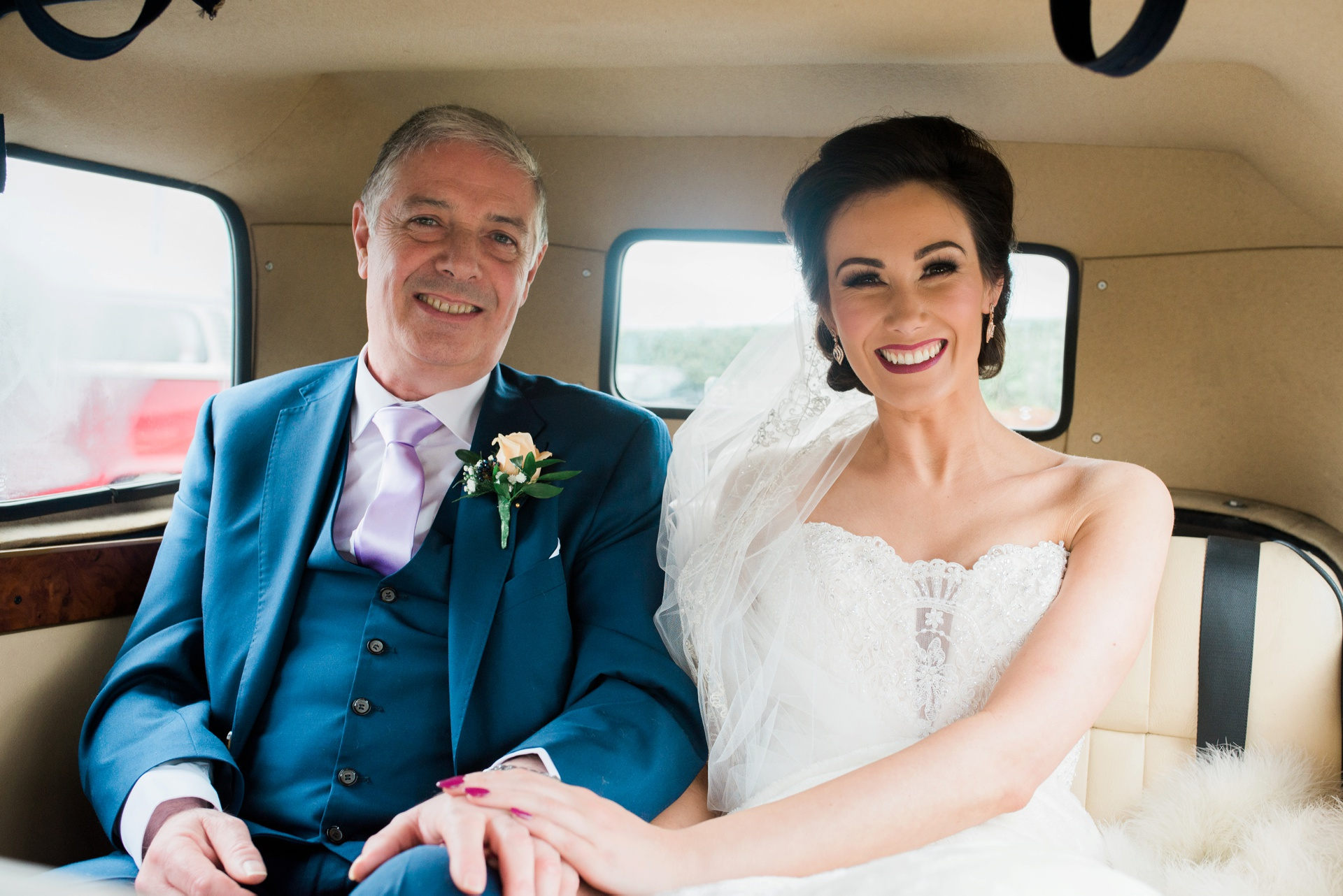 Bride with father of the bride in car