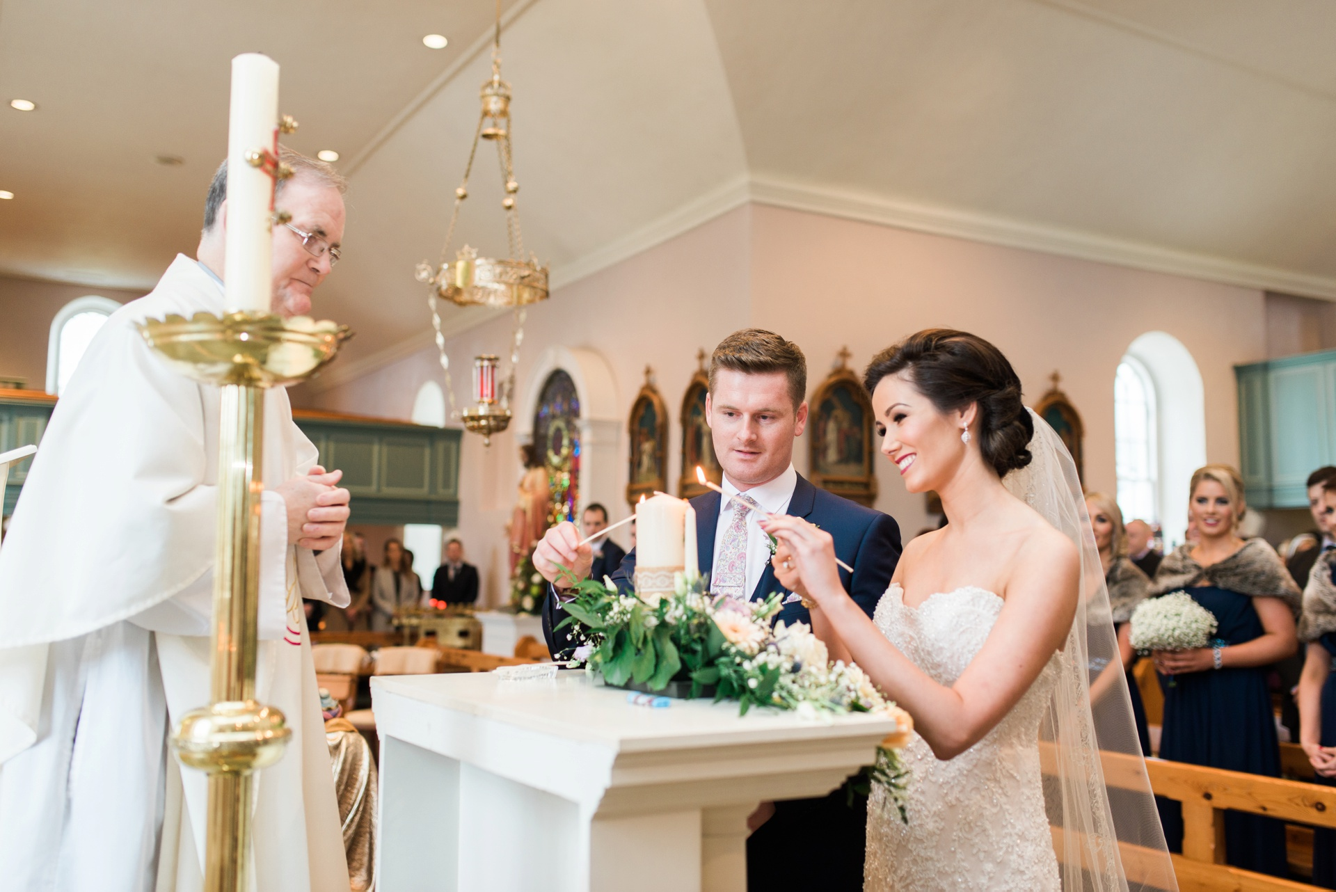 Bride and groom lighting candles in church