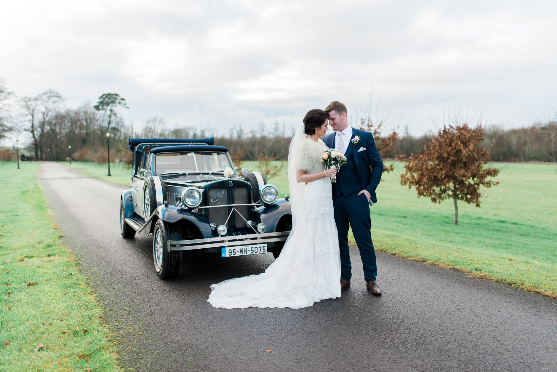 Bride and groom together with vintage car