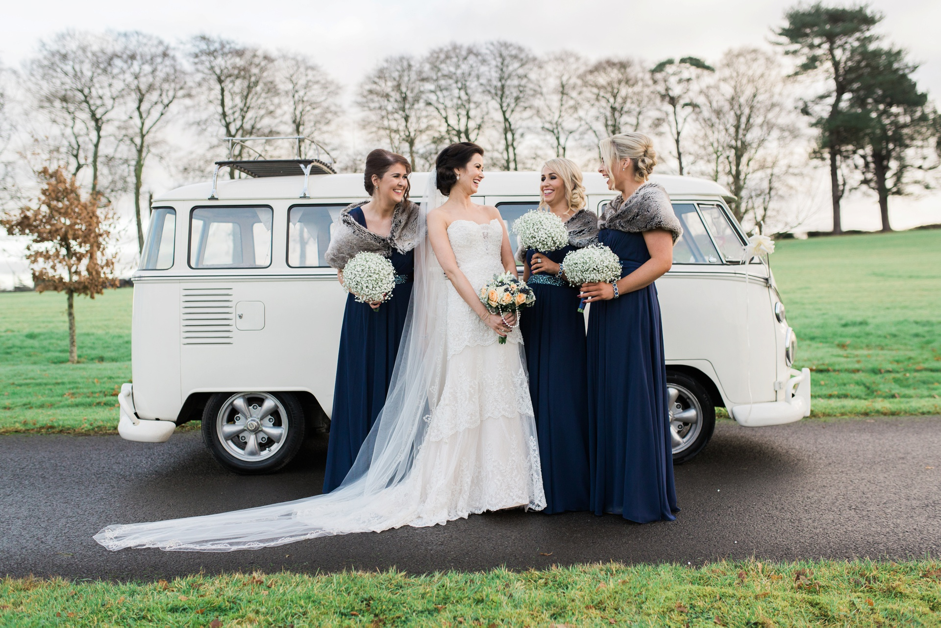 Bride and bridesmaids together beside white Volkswagon camper van