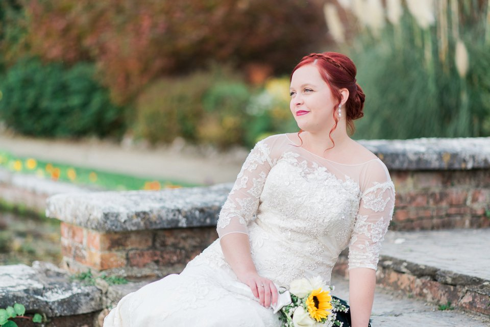 Red haired bride sitting down holding bouquet
