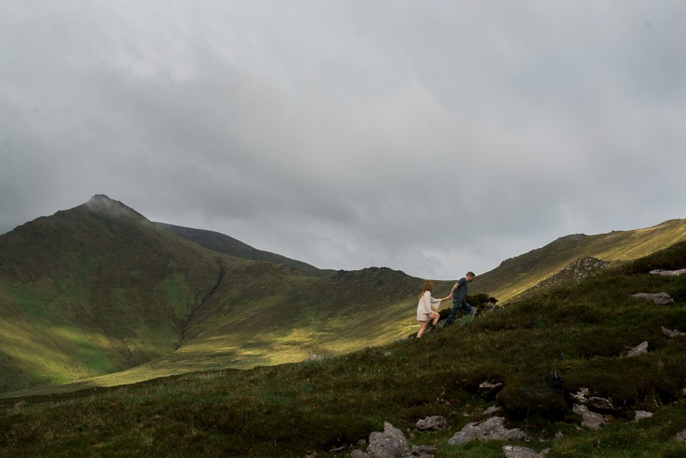 Man and woman climbing up kerry mountains