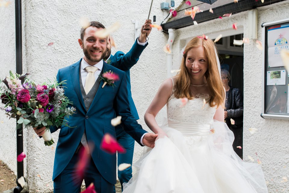 Bride and groom with confetti walking outside church