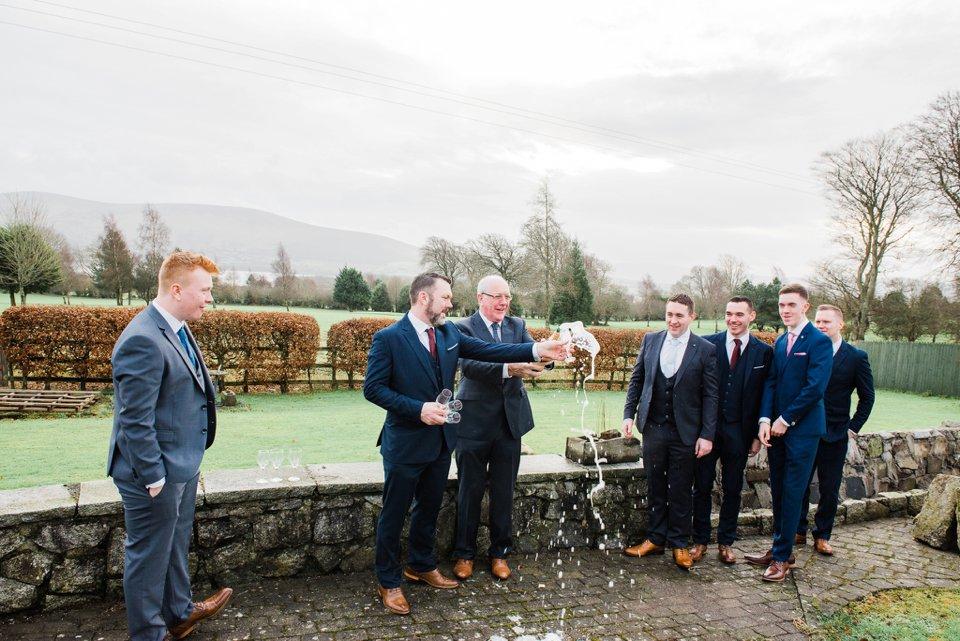 Grooms men open champagne outside