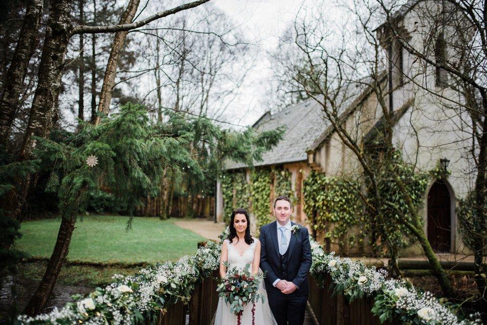 Bride and groom stand on bridge facing camera
