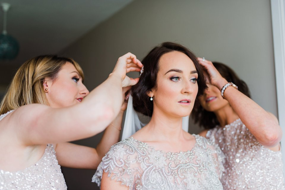 Bride getting hair fixed with bridesmaids