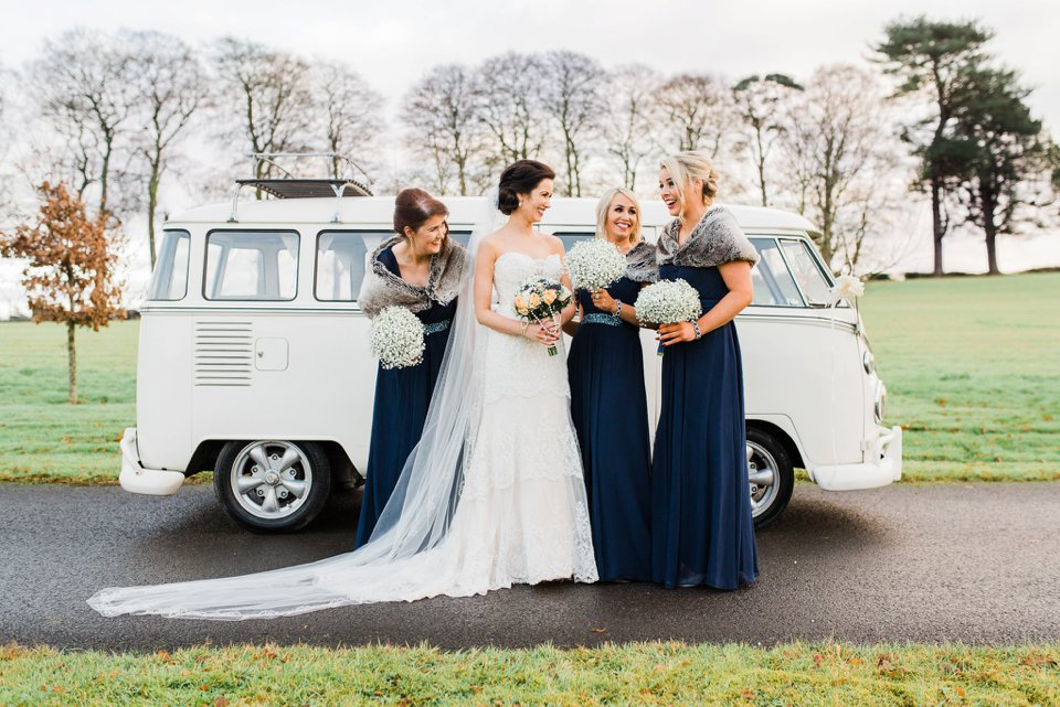 Bride and bridesmaids laughing with white camper van