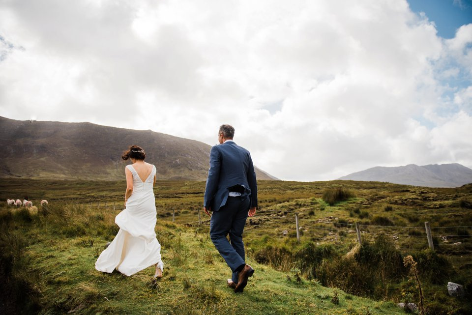 Bride and groom walking in field with sheep