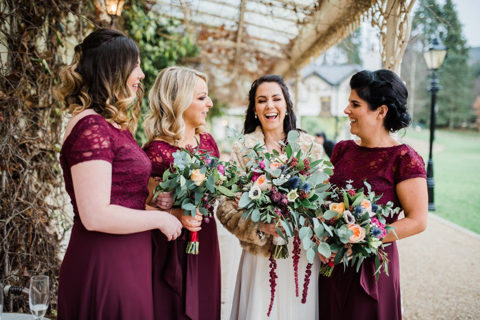 Bride and bridesmaids laughing in burgundy dresses and holding bouquets