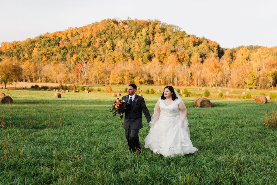 Bride and groom walking with hay bales in Tennessee