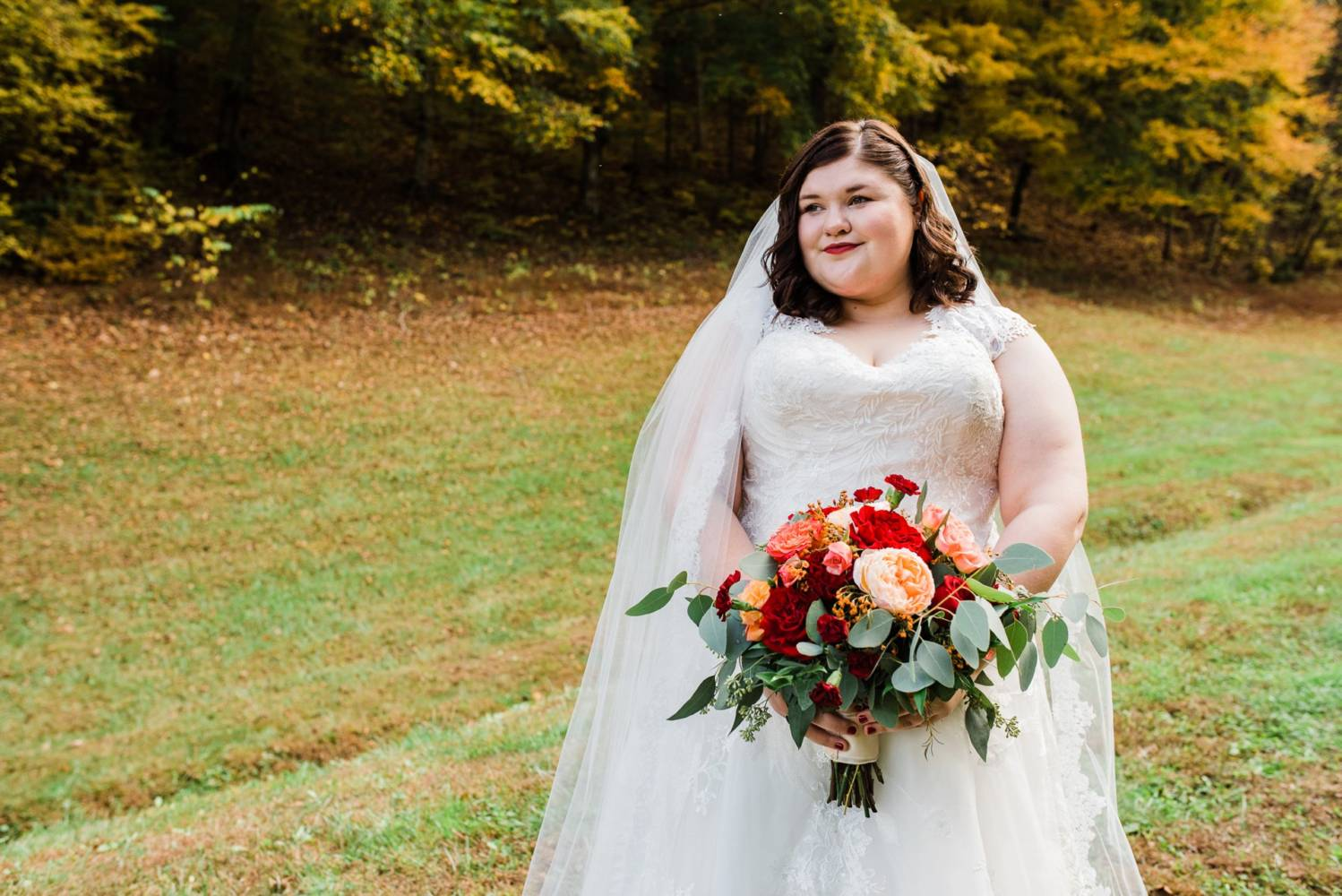 Autumn wedding bride with red and orange bouquet