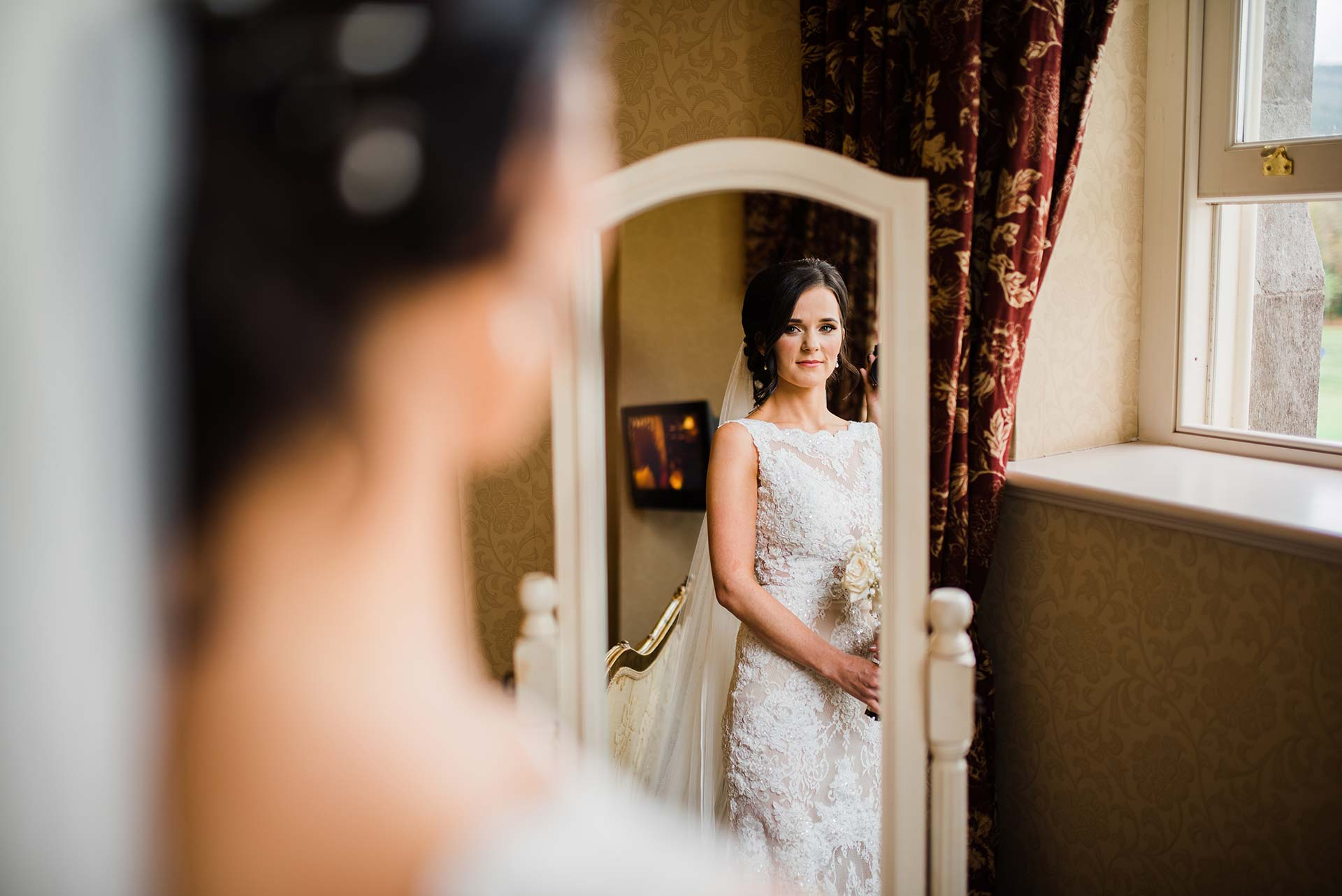 bride in a-line lace dress looks at herself in the mirror