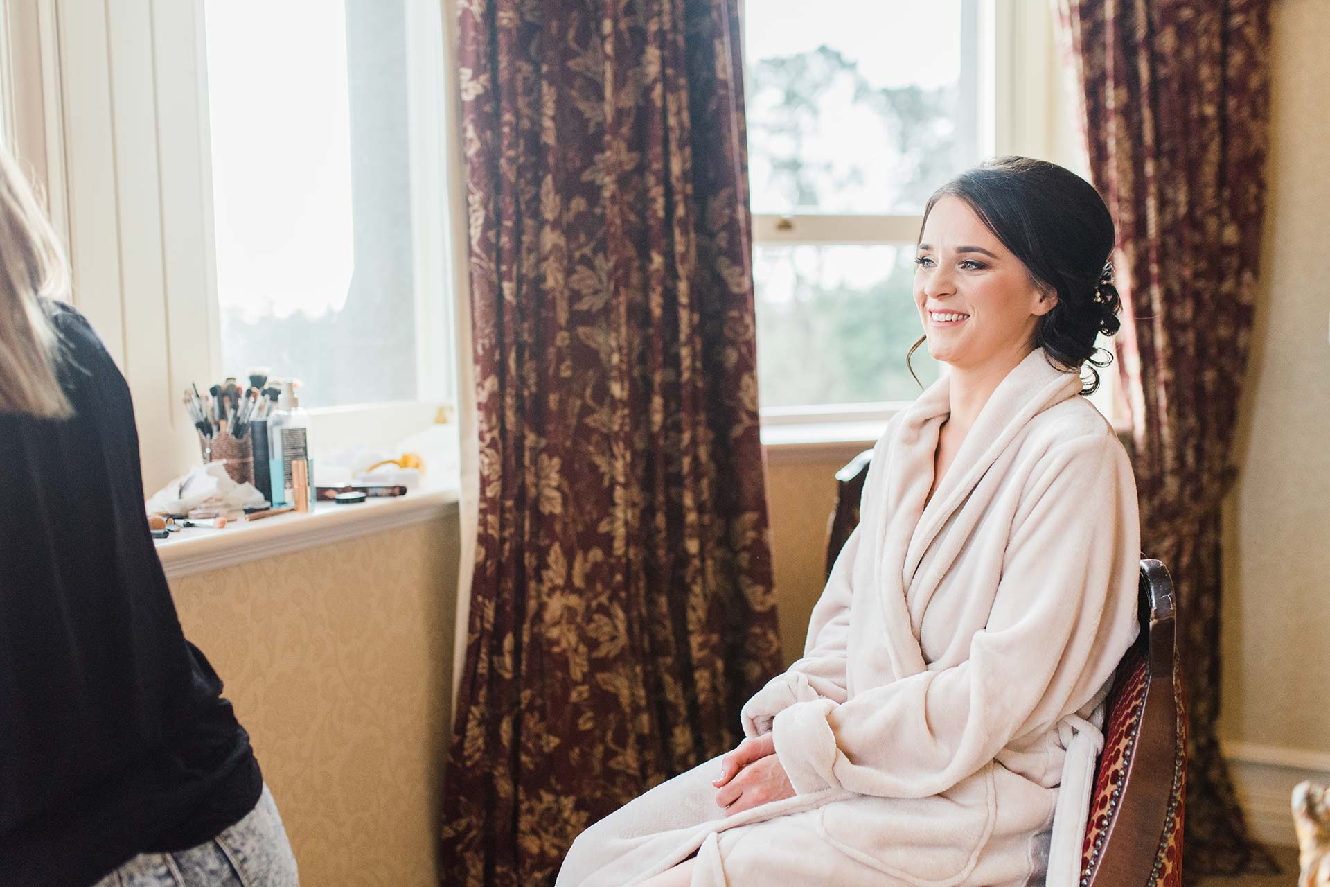 bride smiles as she is getting ready for her wedding in Ireland