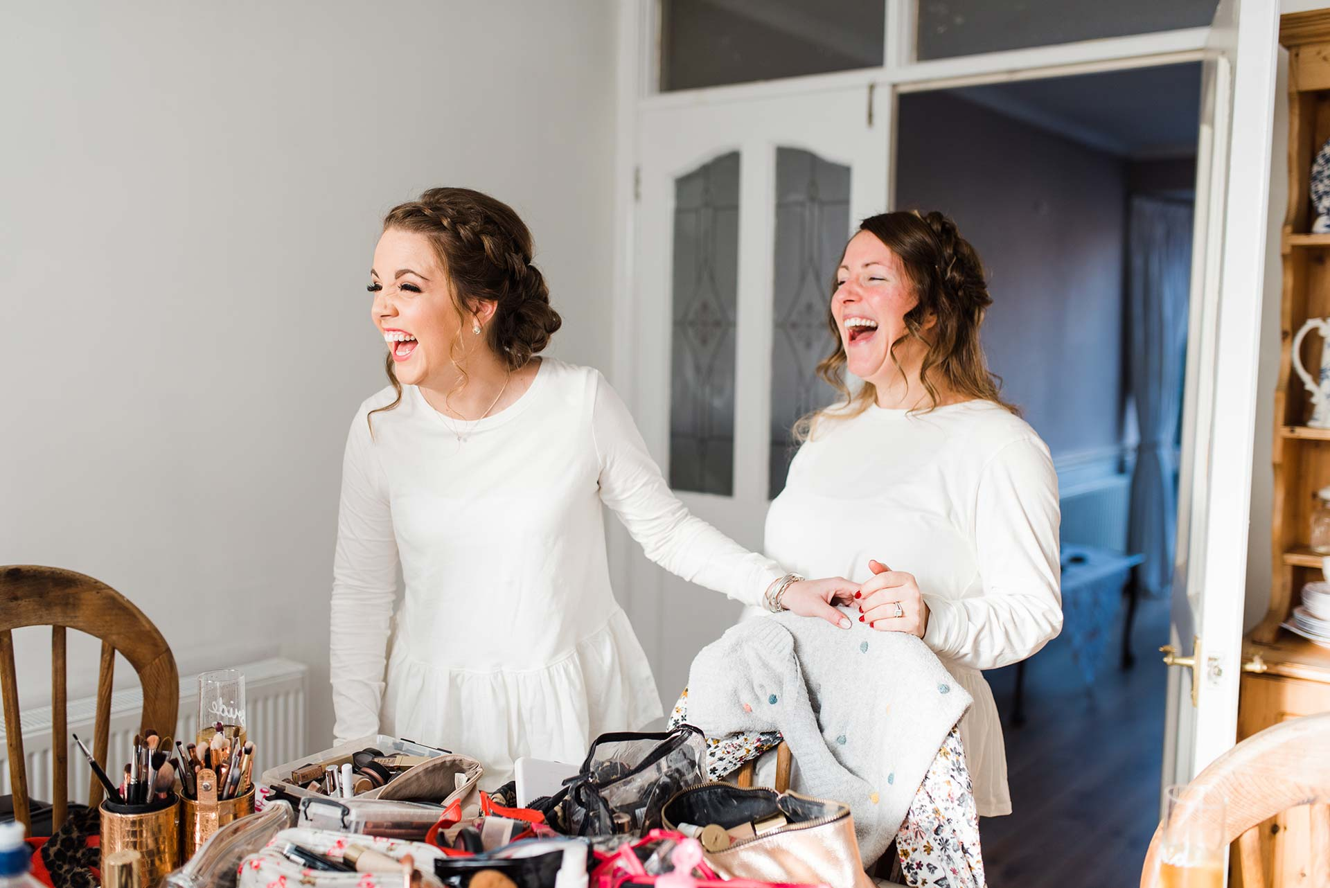 bridesmaids laugh while getting ready for wedding