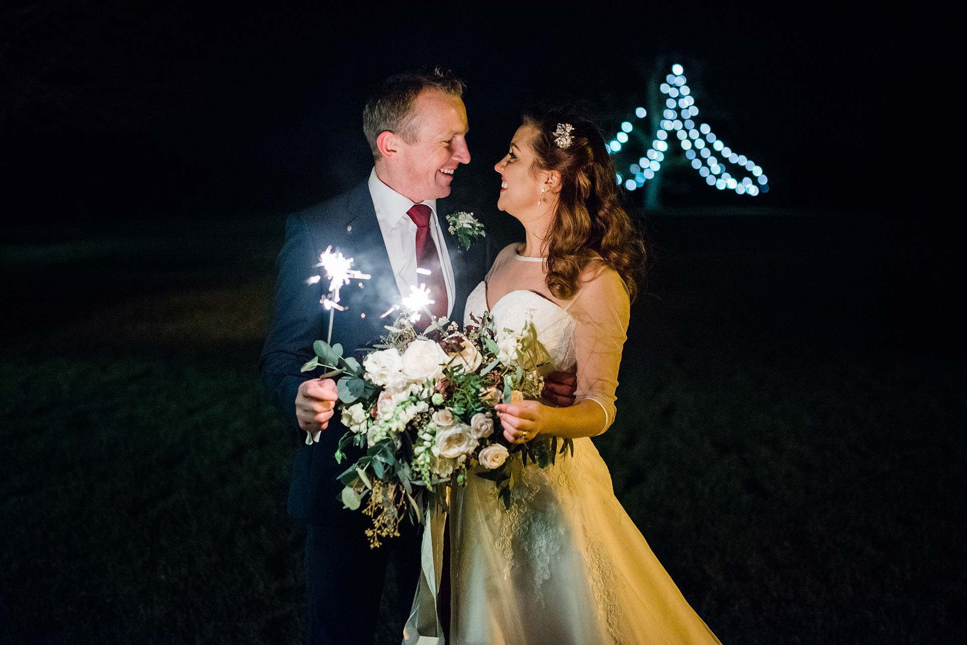 bride and groom look at each other as they hold sparklers