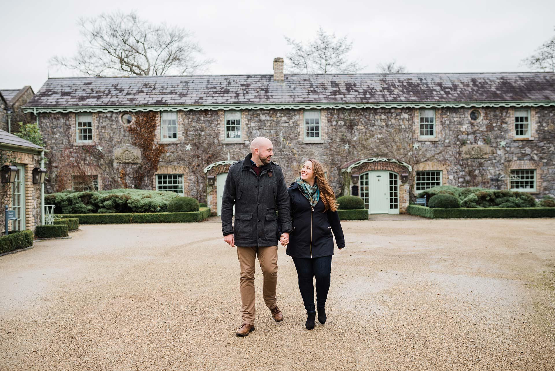 man and woman walk hand in hand away from luxury Irish countryside home