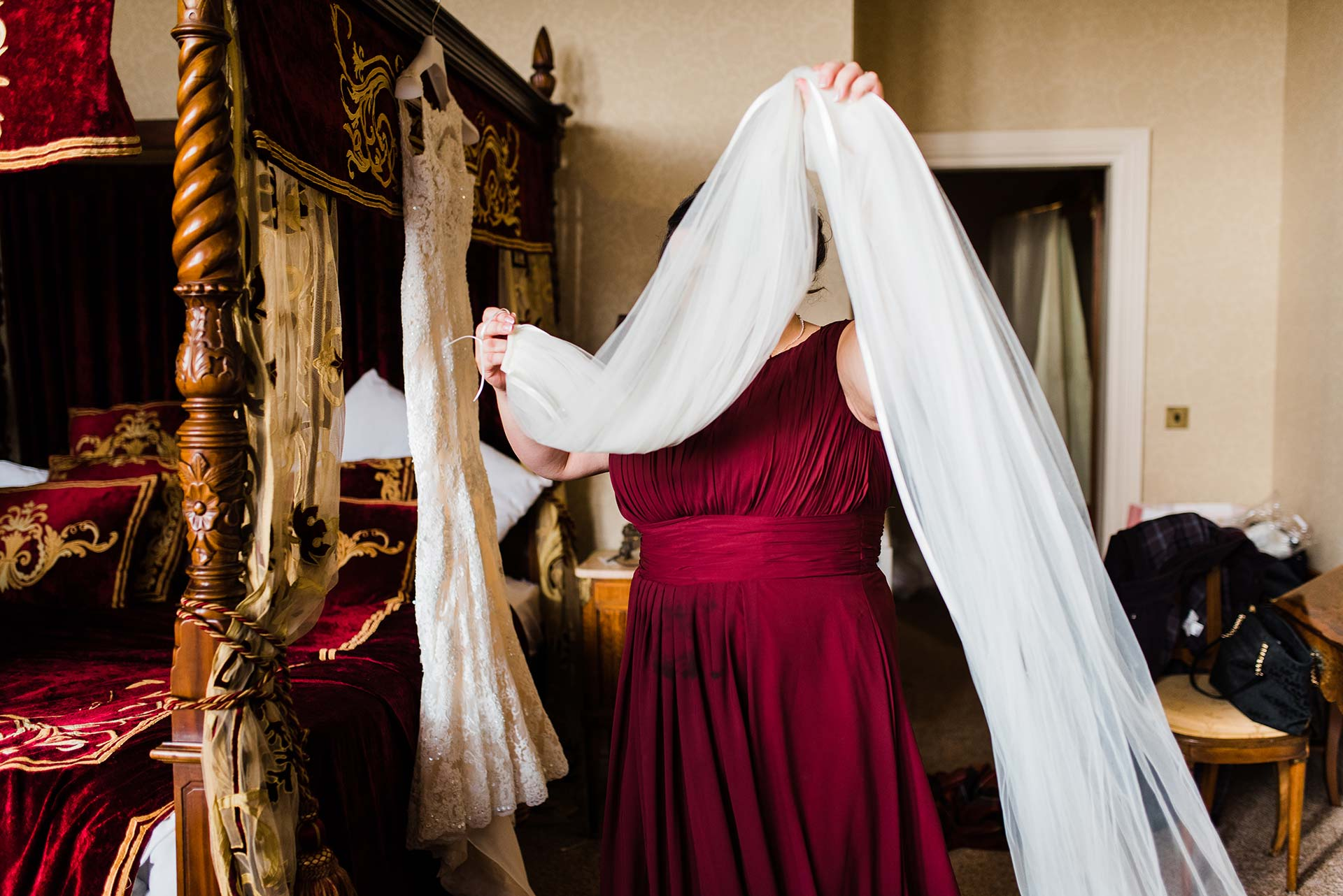 bridesmaid carries long wedding veil
