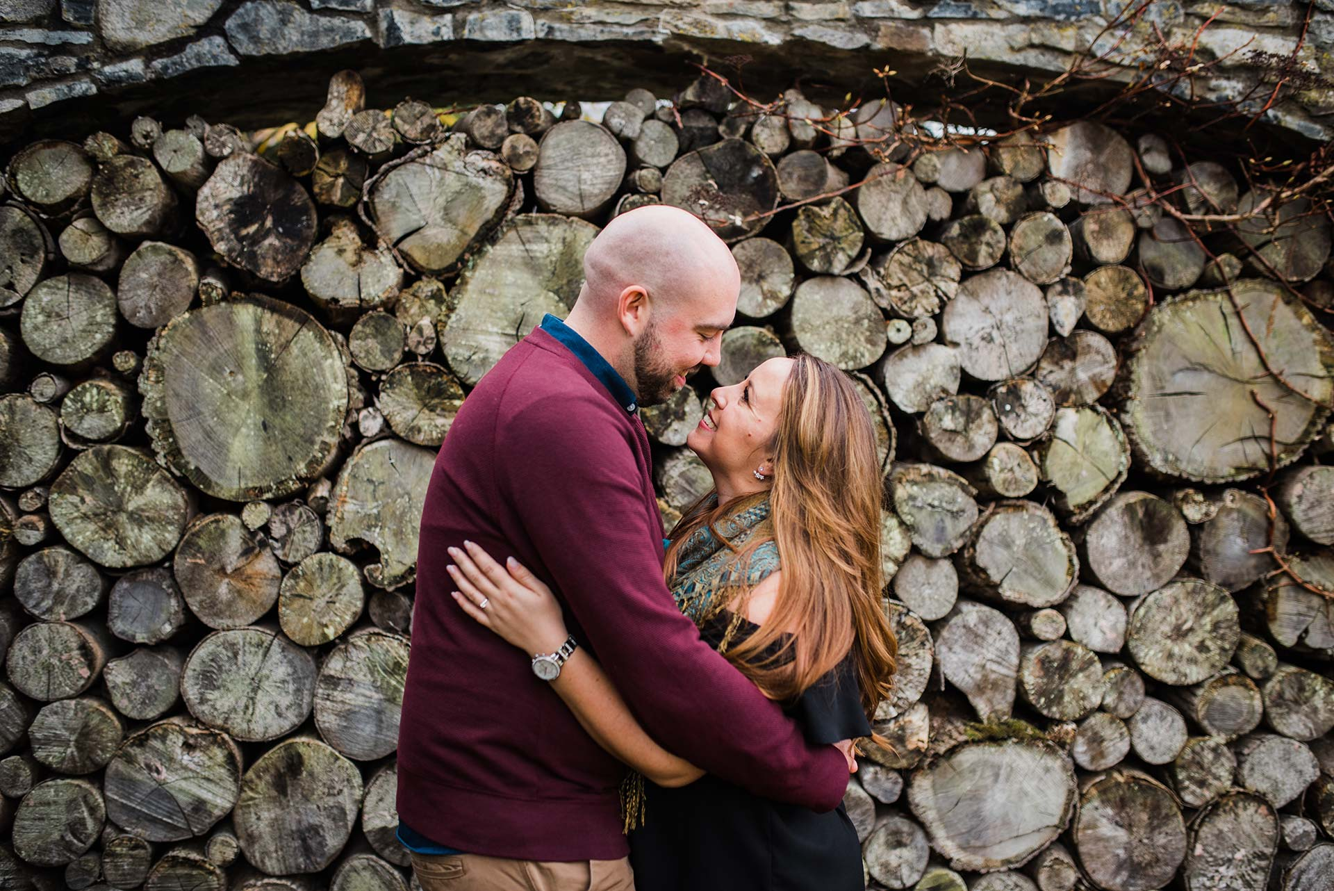 couple stands in front of stacked wood at the Cliff at Lyons