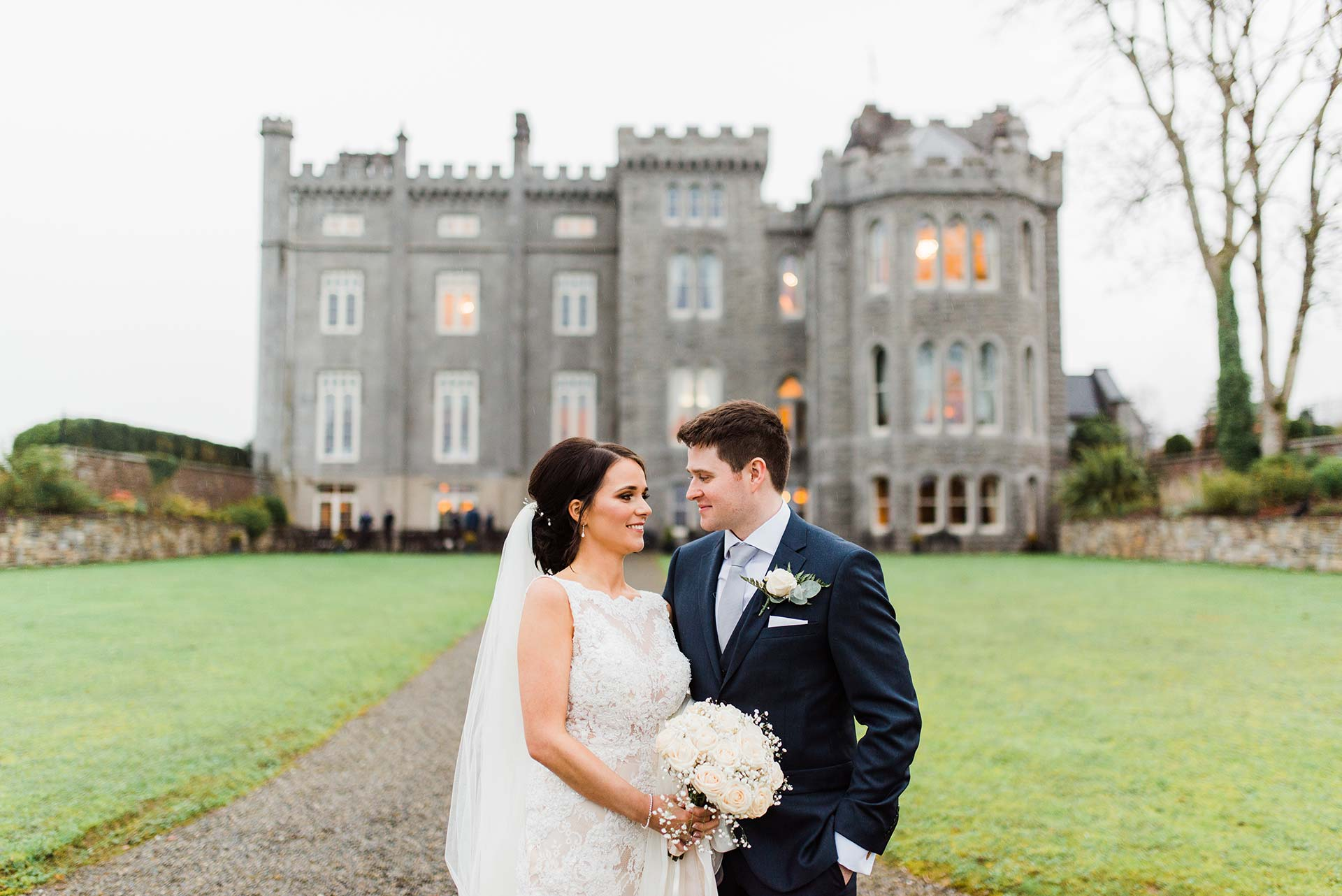bride and groom look at each other in front of Kilronan Castle in Roscommon Ireland