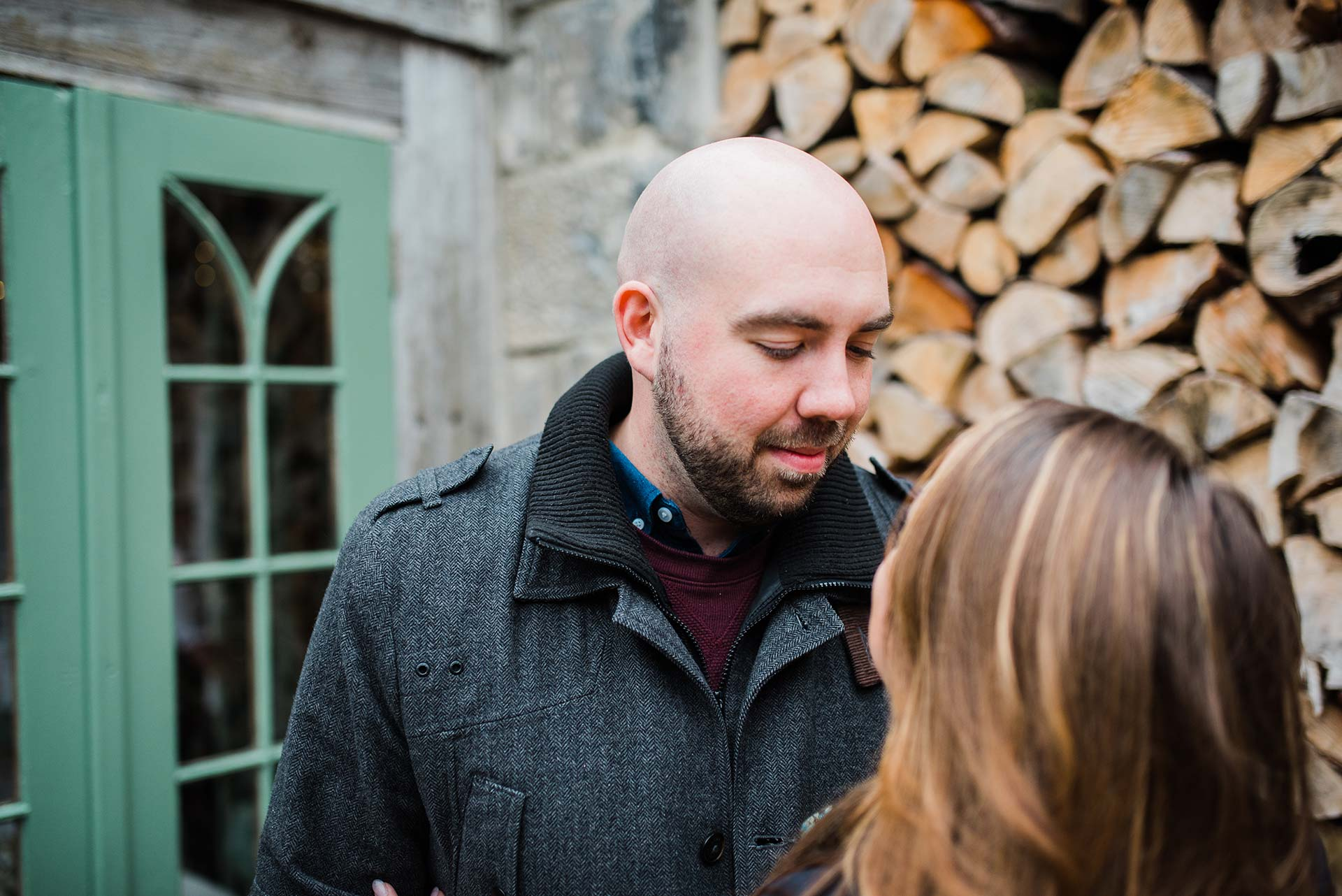 man in heather gray jacket looks at his fiancée