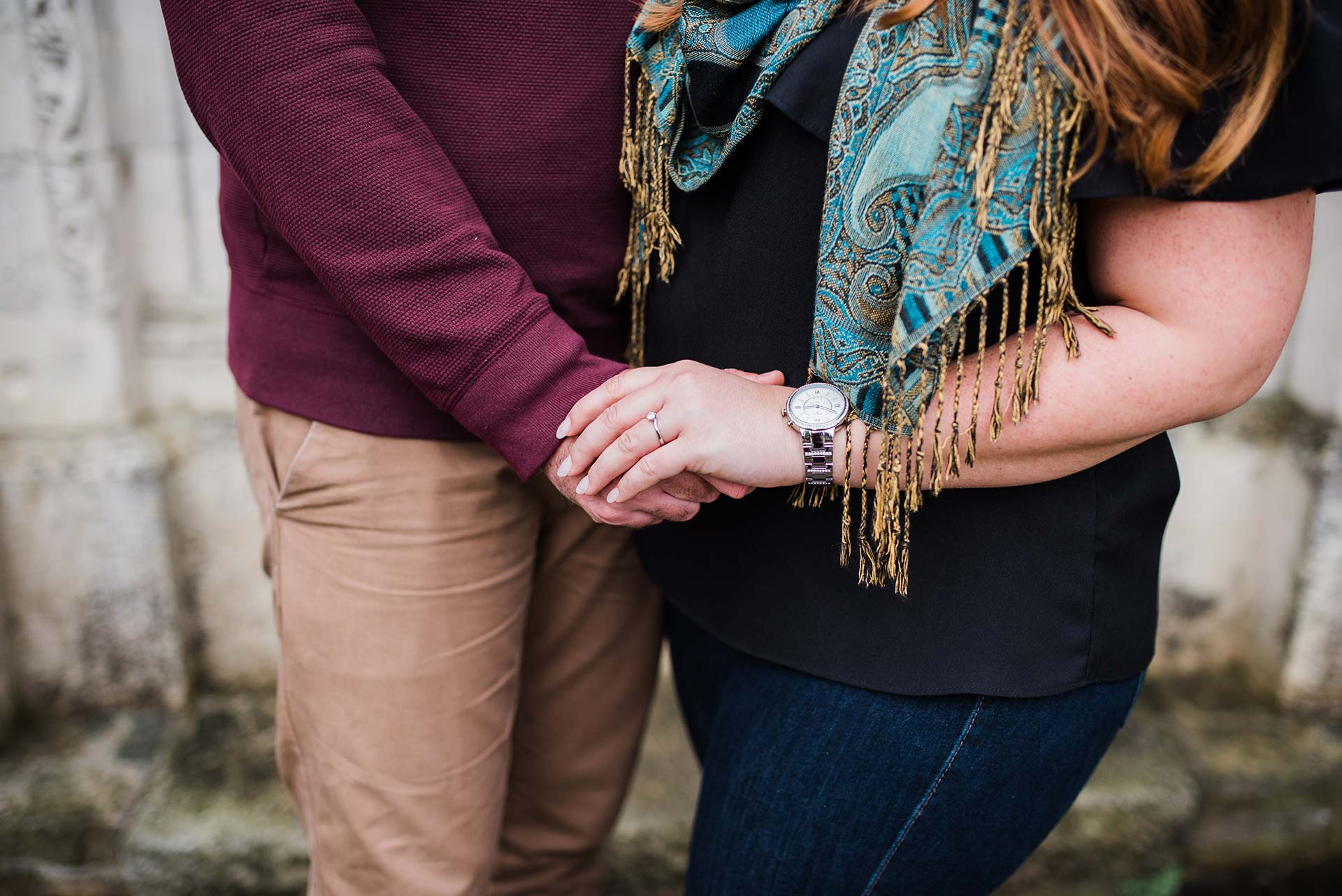 engaged couple holds hand and show engagement ring