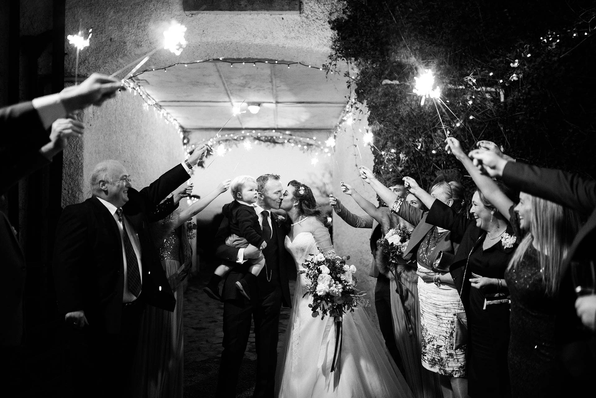 black and white portrait of bride and groom exiting their wedding reception