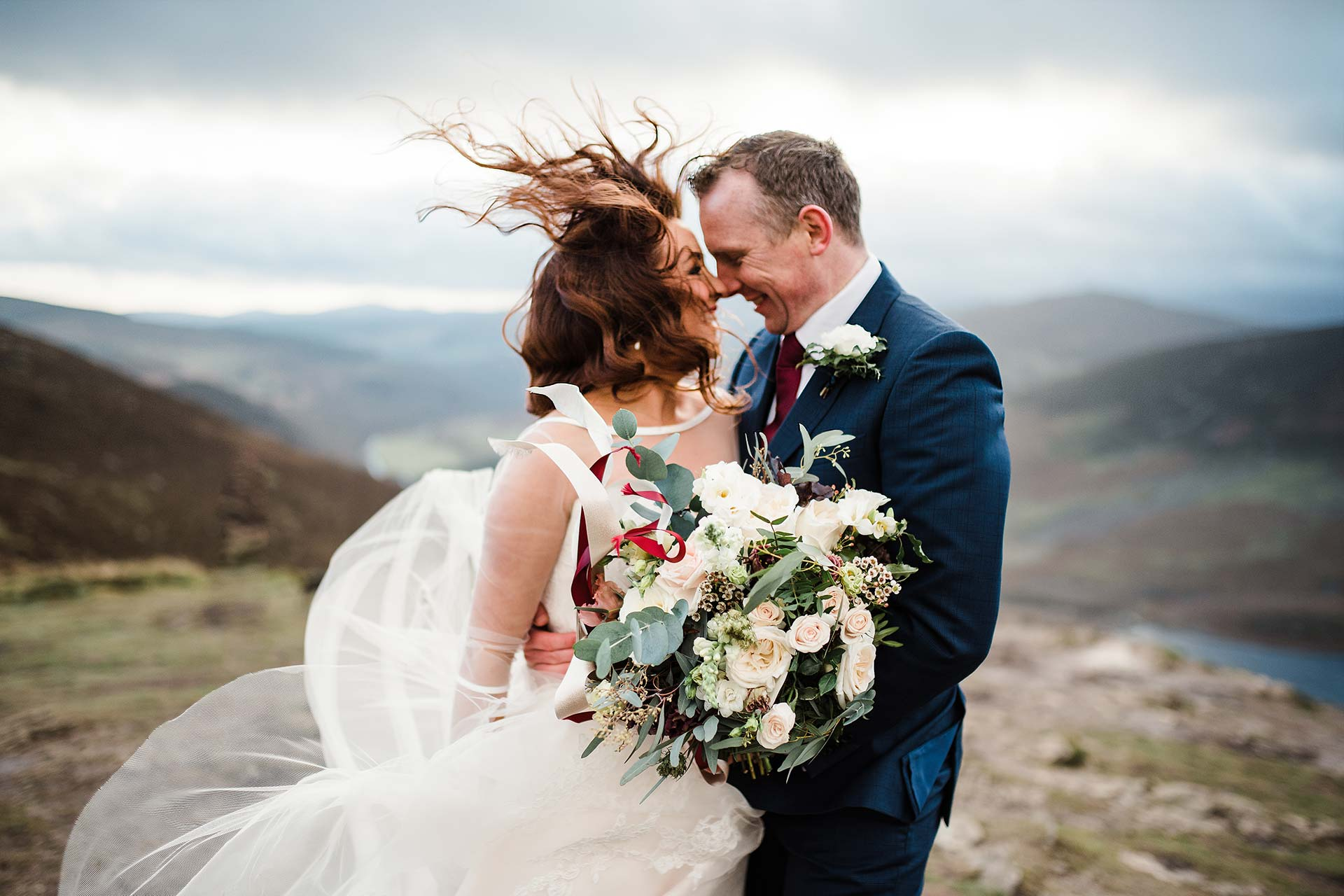 windswept bride and groom look at each other on top of Wicklow Mountains