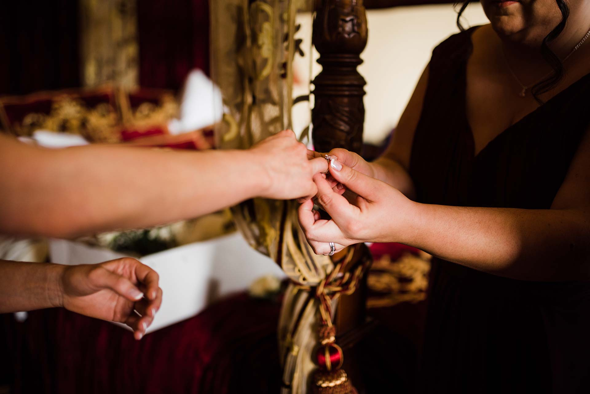 bridesmaid put engagement ring on brides right hand before wedding ceremony