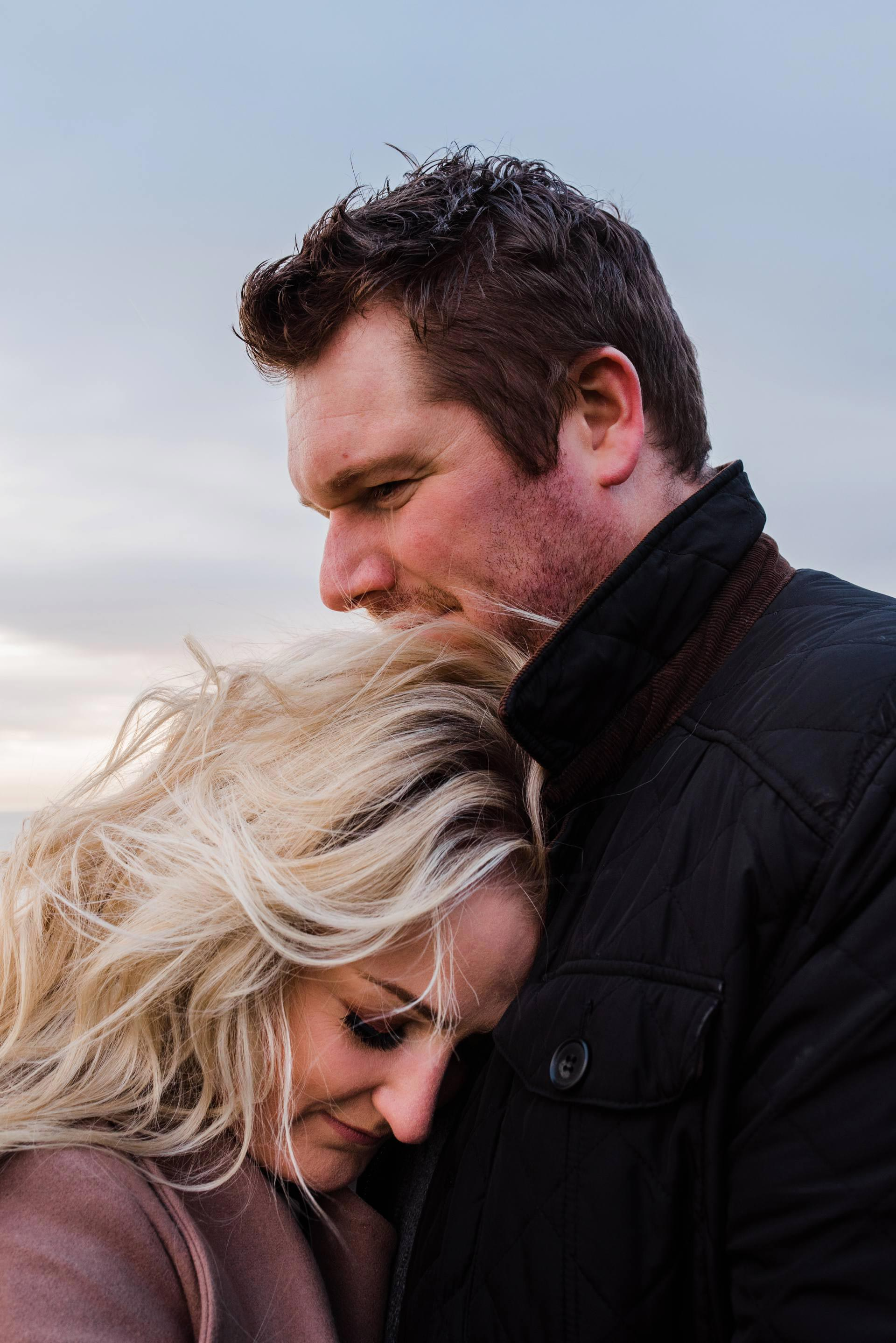 A Blonde woman rests her head on her fiancés chest