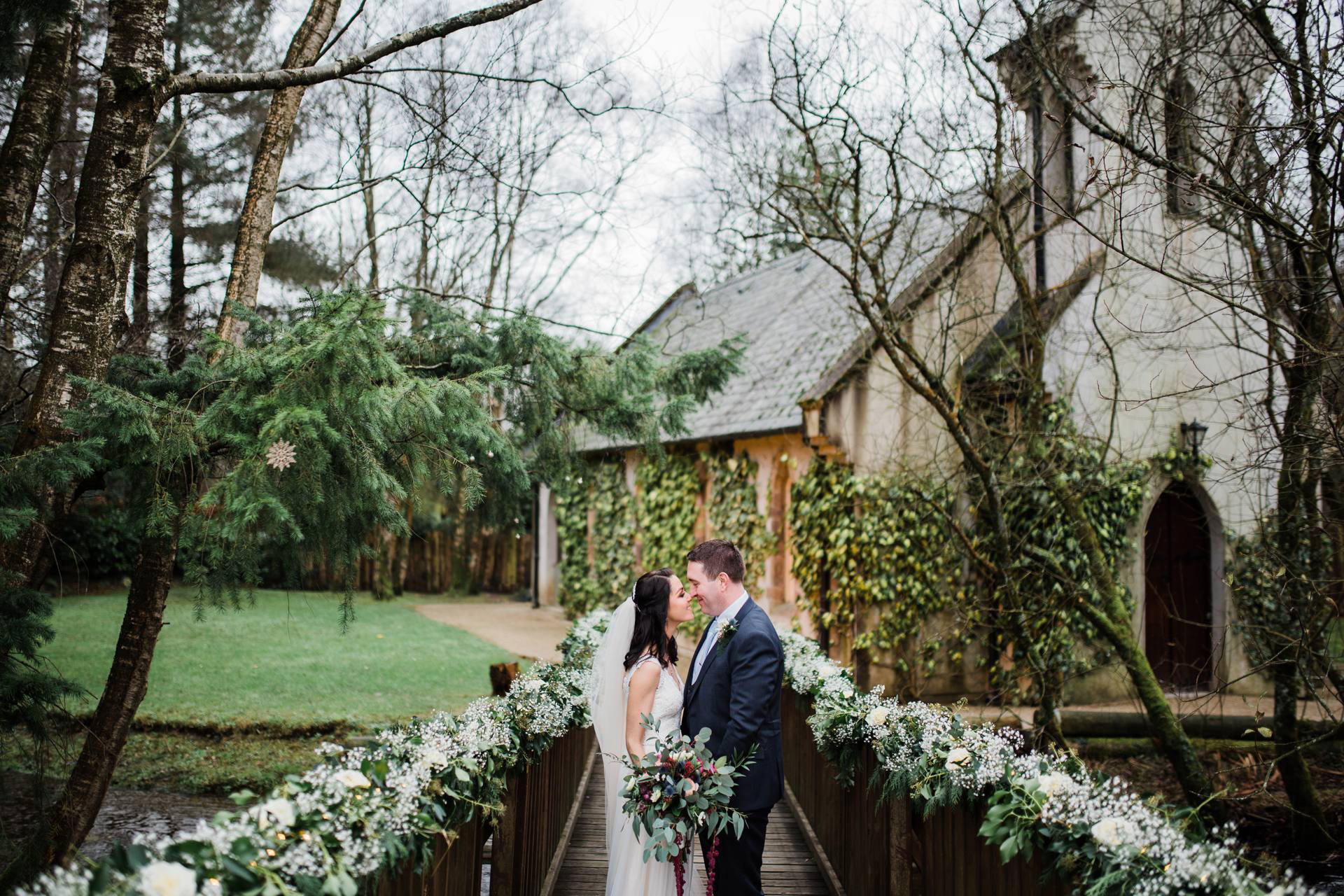 bride and groom are nose to nose on little bridge in front of ivy covered chapel