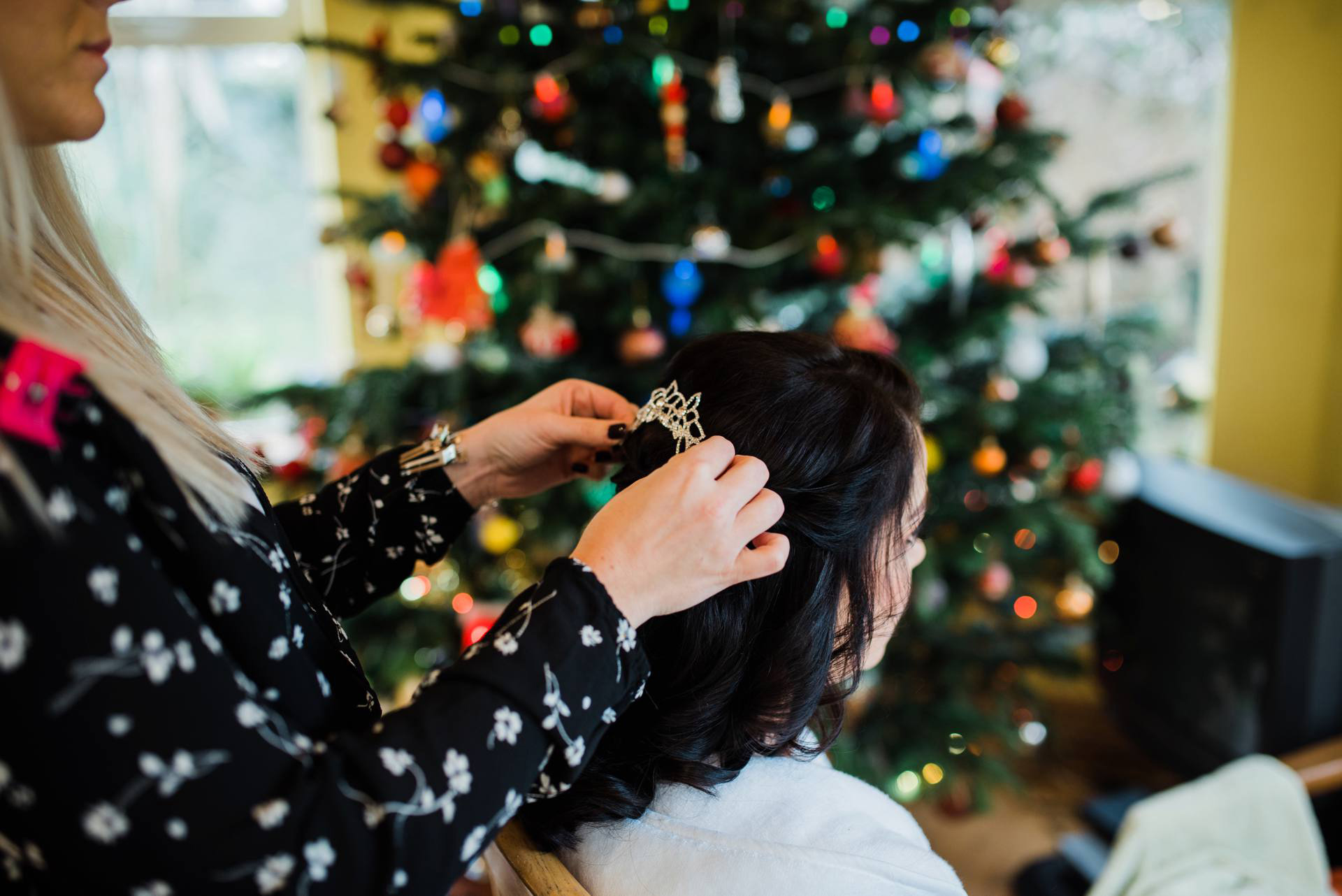 woman place tiara in brides hair in front of Christmas tree