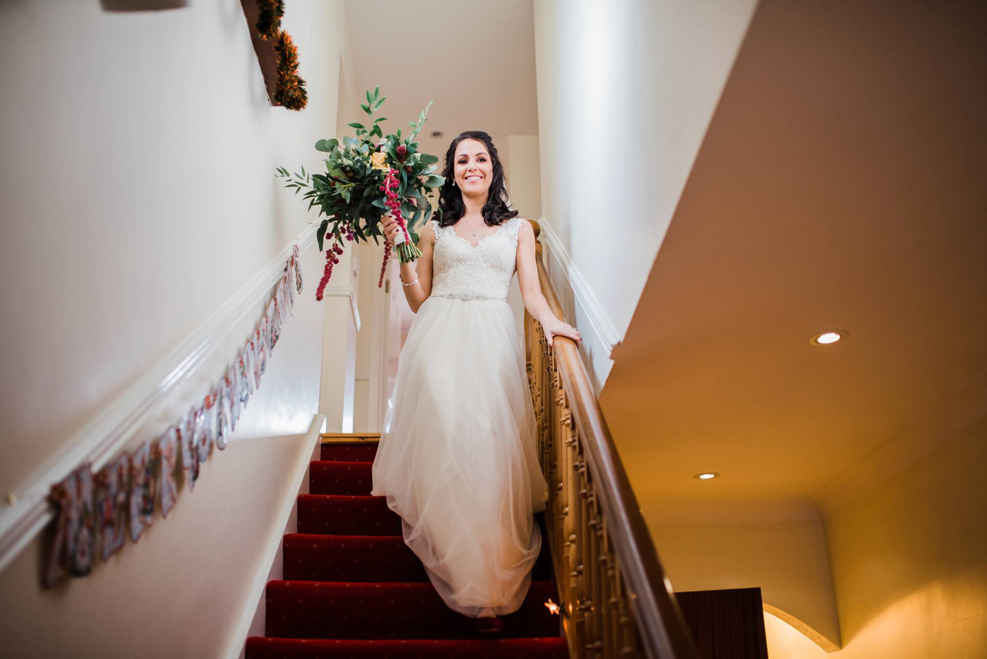 bride carrying bouquet walks down stairs