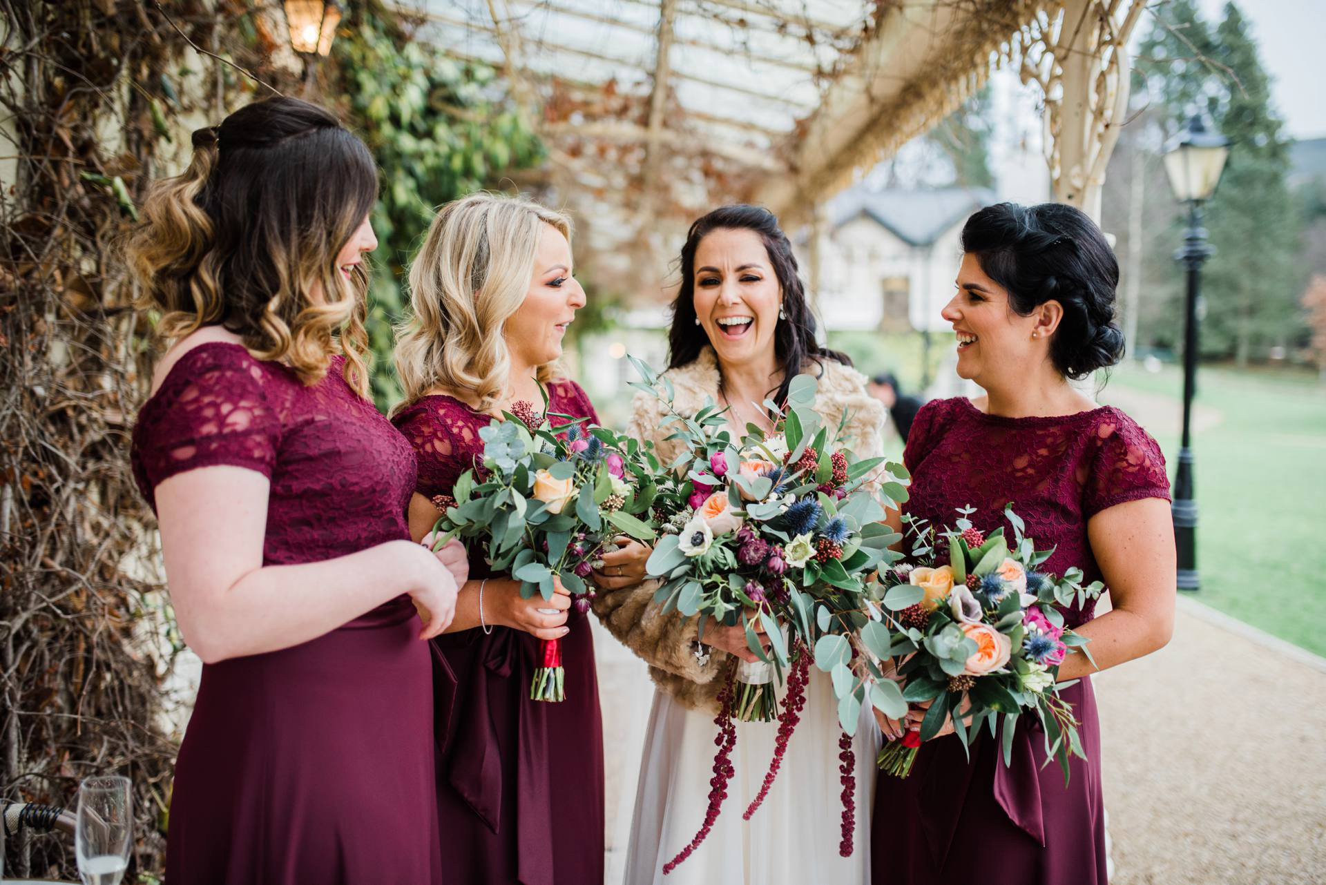 bride laughs with her Burgundy clad dressed bridesmaids