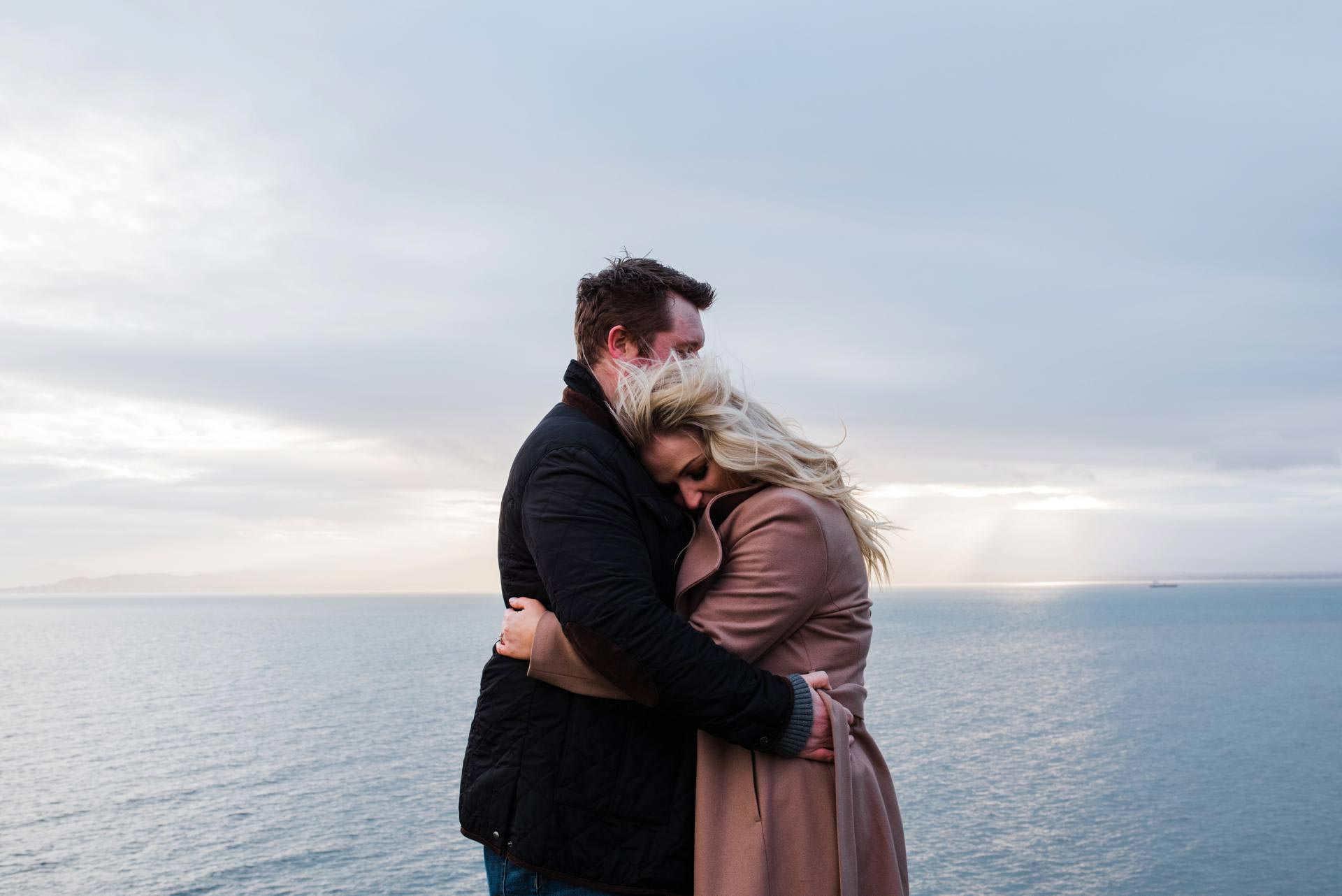Engaged couple hugs on Howth Cliffs in Dublin Ireland
