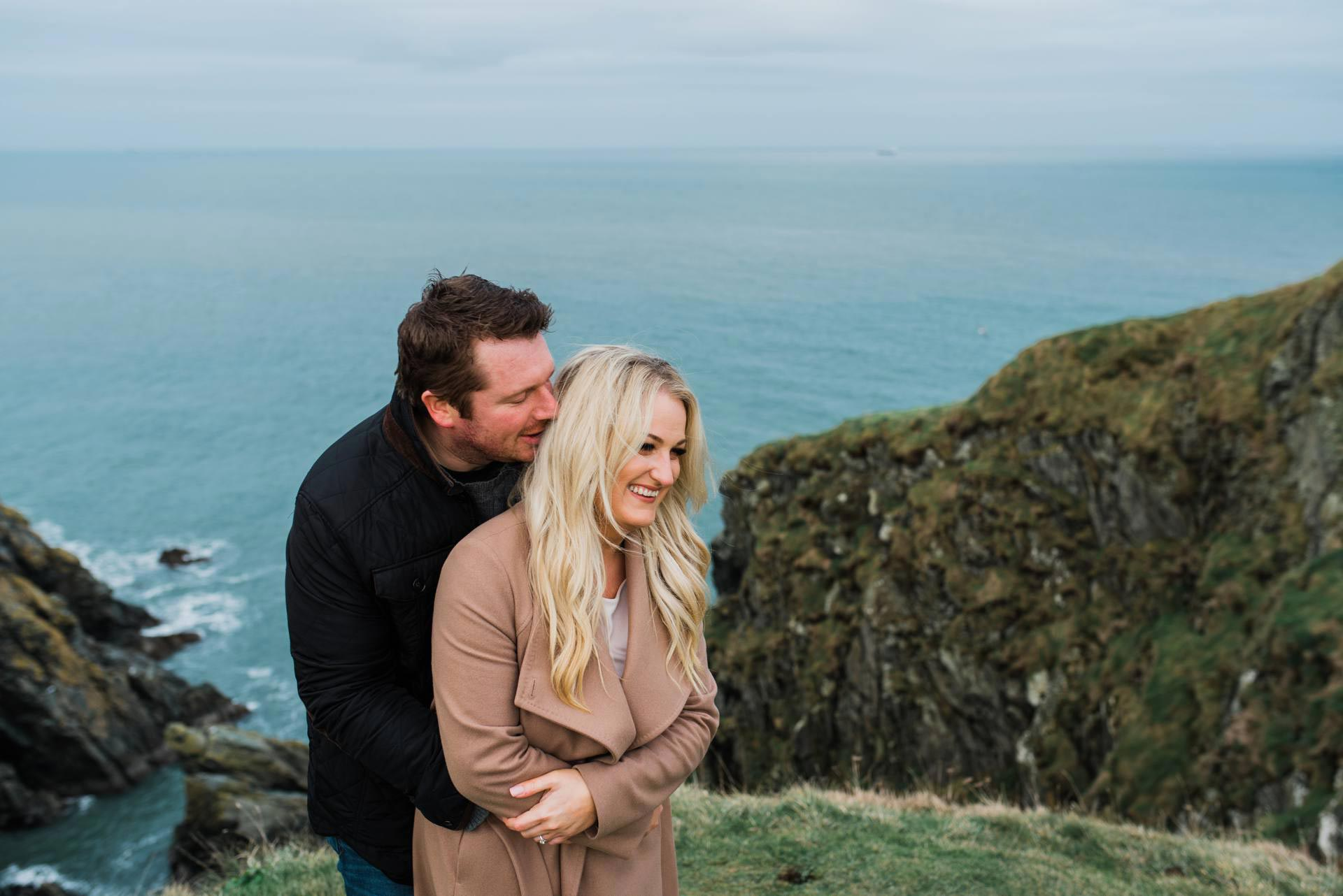 engaged couple laugh while hugging on Howth cliffs in Dublin Ireland