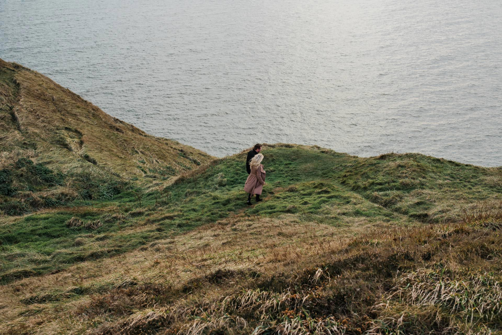Couple walks along Howth Cliffs during sunset