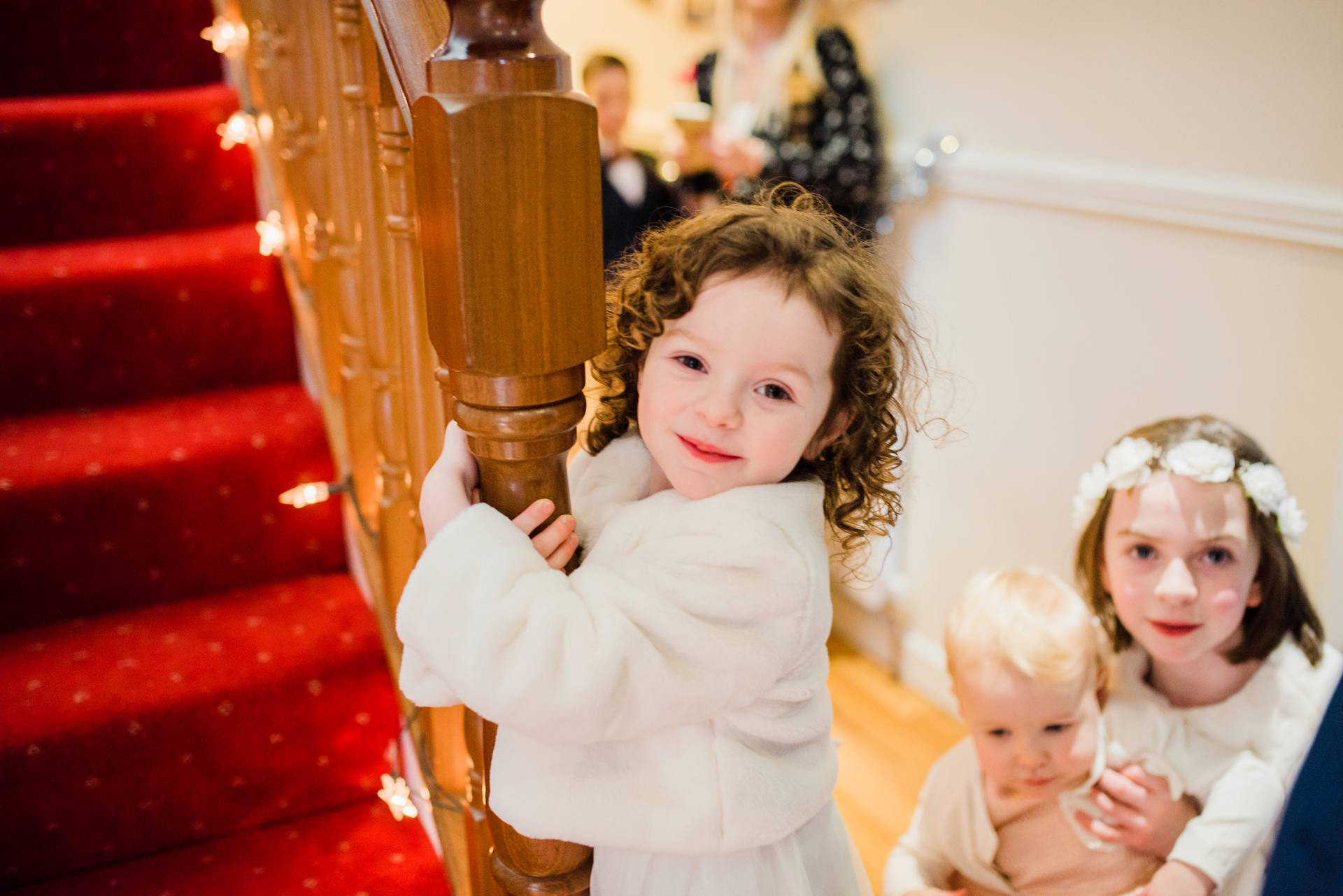 Flowergirl looks at camera while hanging onto stair railing