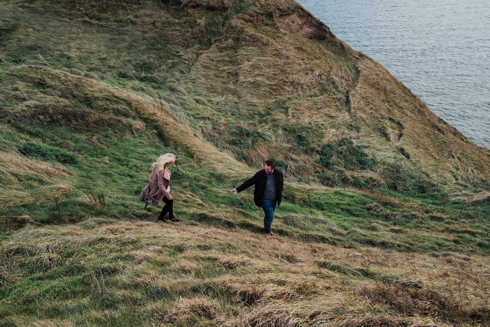 Man reaches for his Fiance while walking along the oceanside cliffs at Howth Cliffs