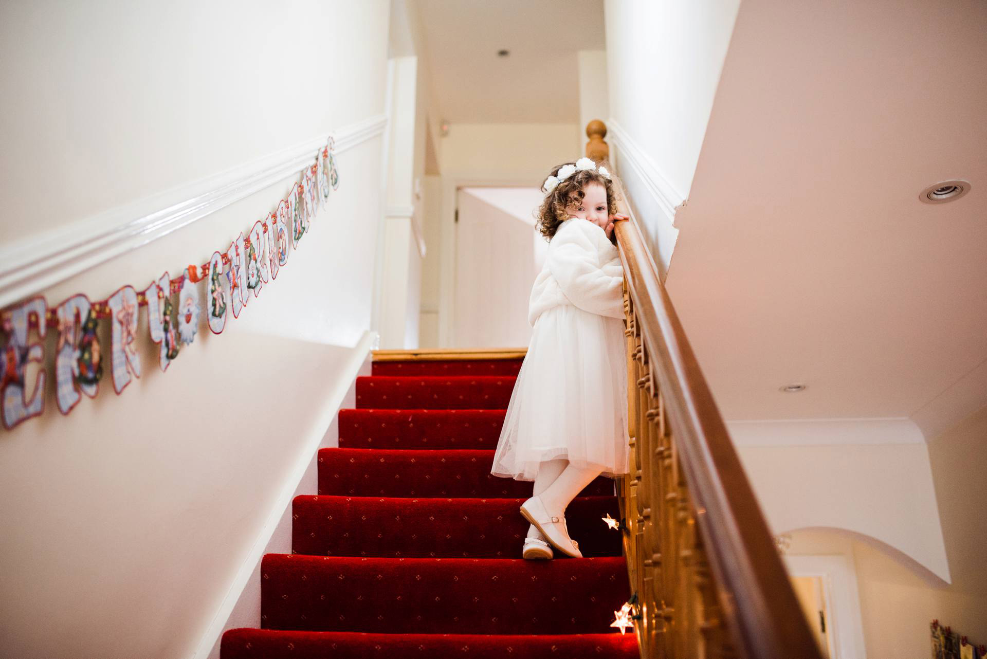 shy little flowergirl looks down staircase over her shoulder