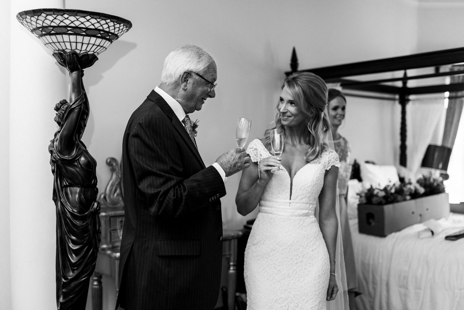 Bride and father smiling and clinking glasses