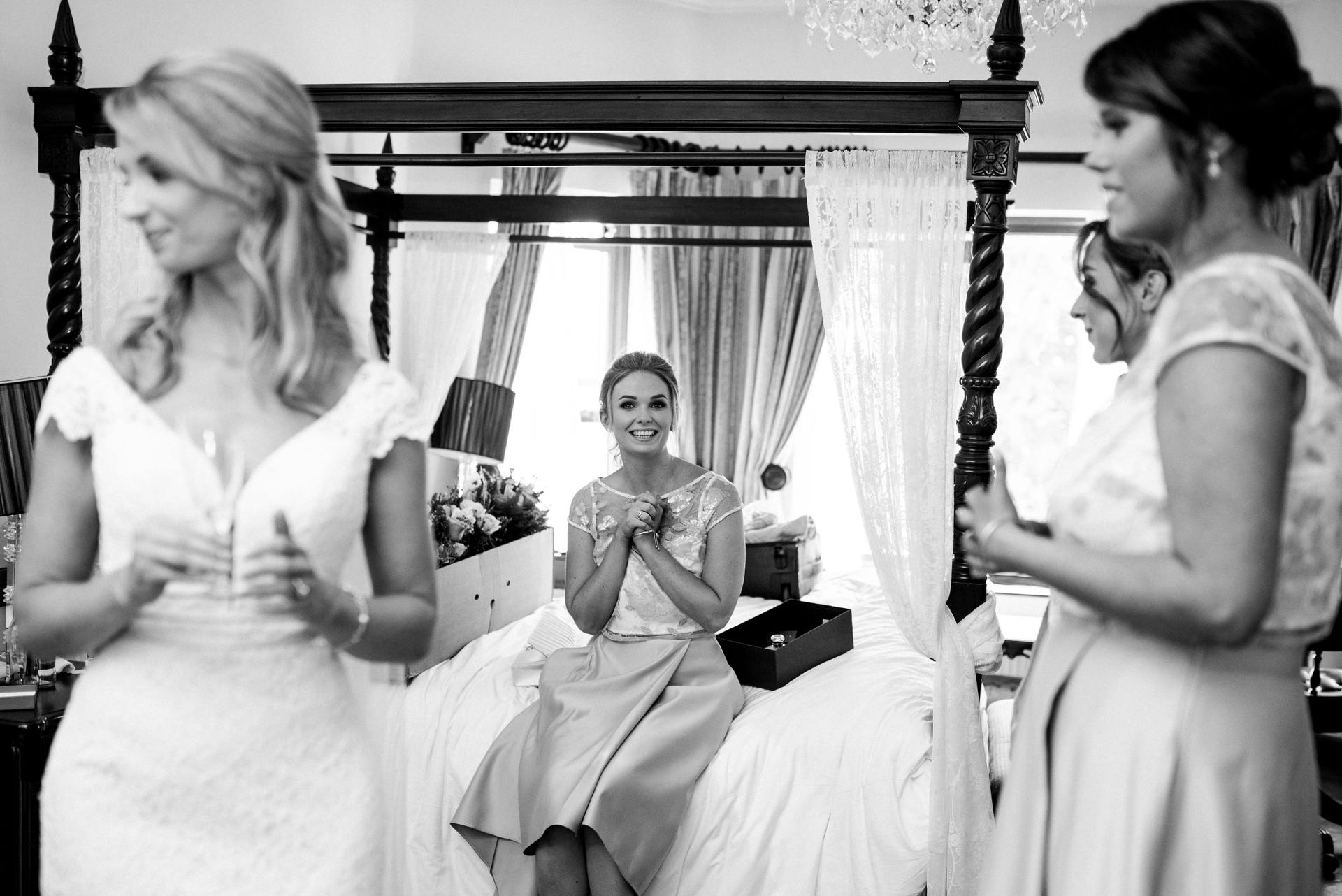 Excited bridesmaid sitting on the bed