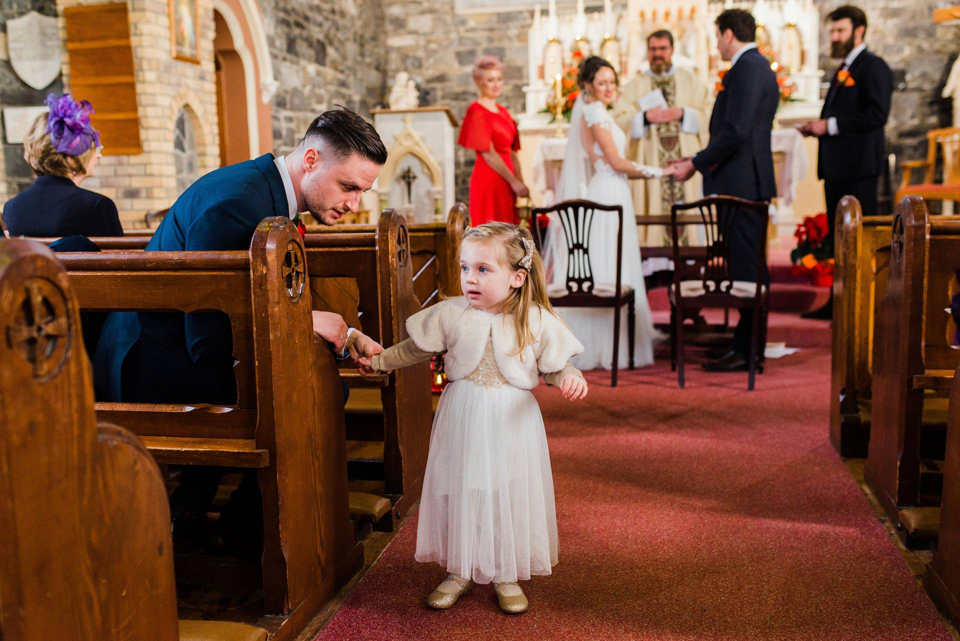 Flower girl running down the aisle in a church