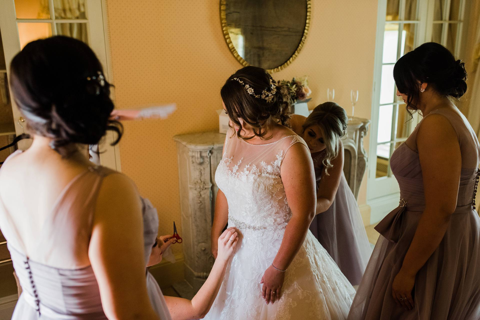 Bride getting ready surrounded by bridesmaids