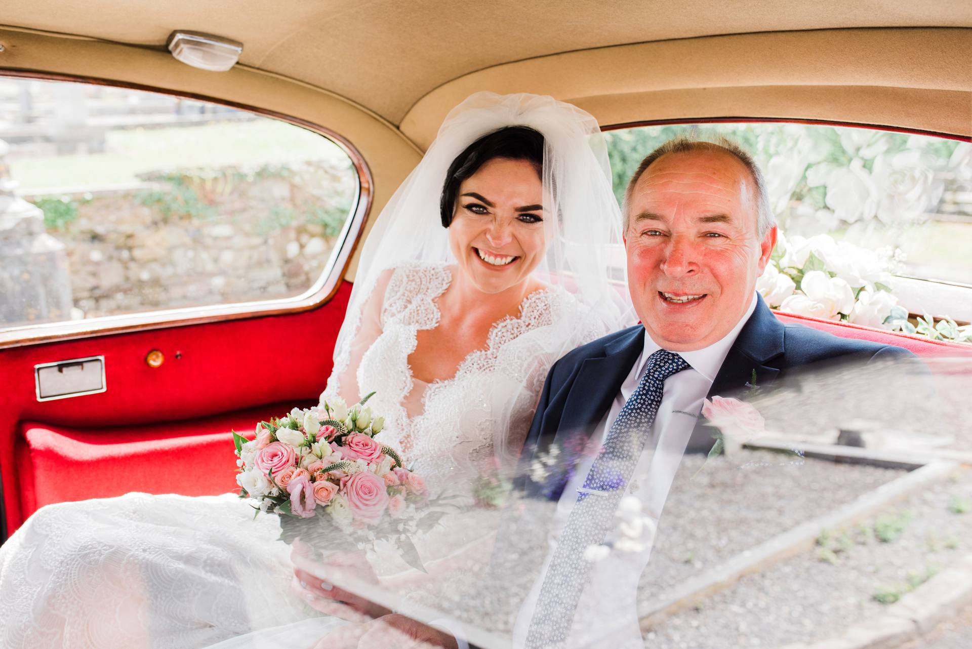 Bride sitting in the backseat of a car with her father