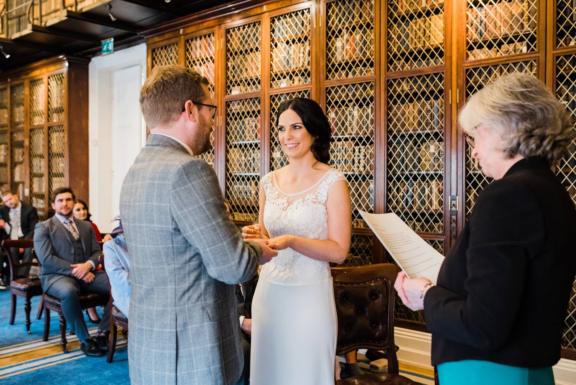 Bride and groom exchanging vows in library