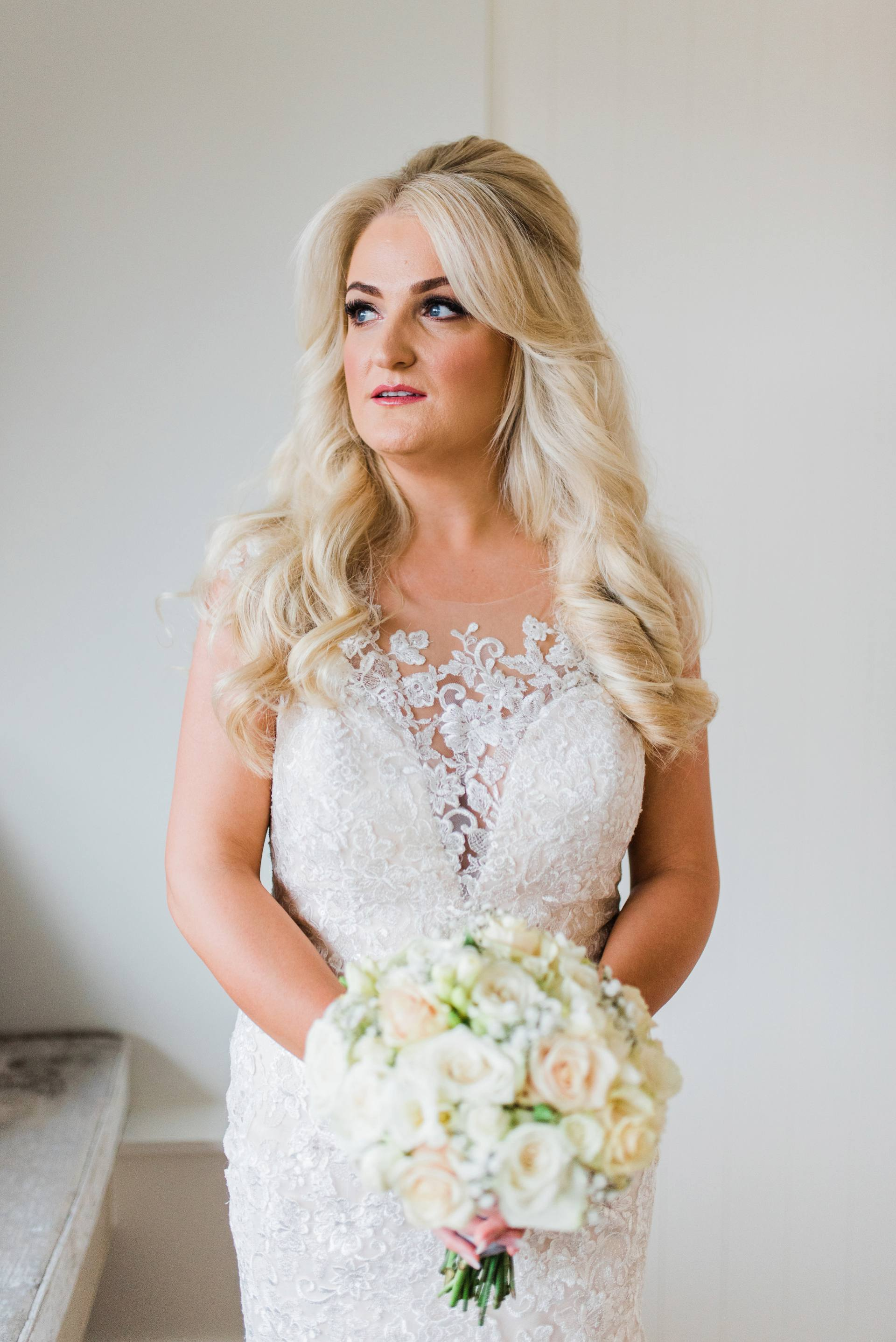 Blonde bride in lace dress holding cream roses