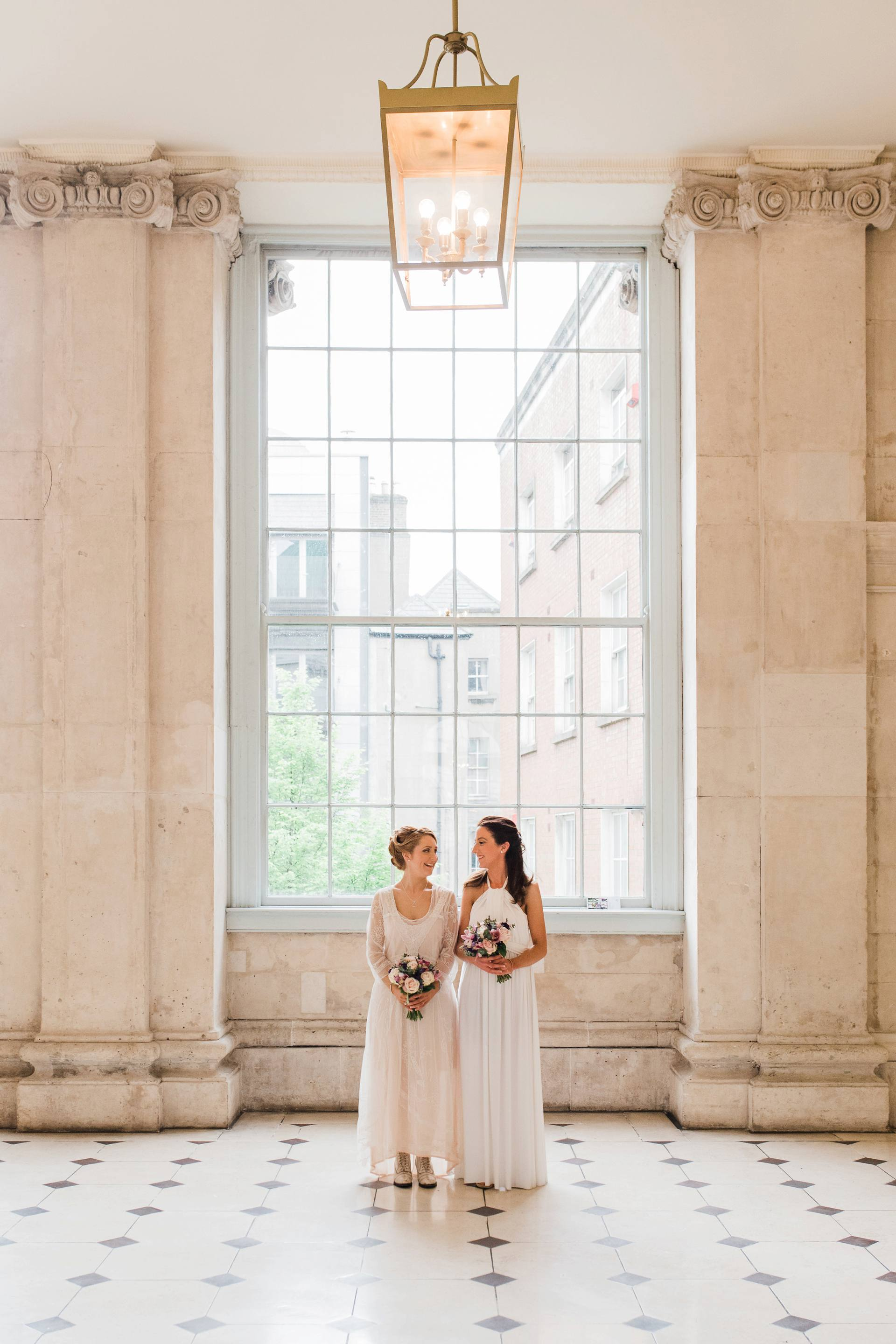 Two brides looking at each other in Dublin City Hall