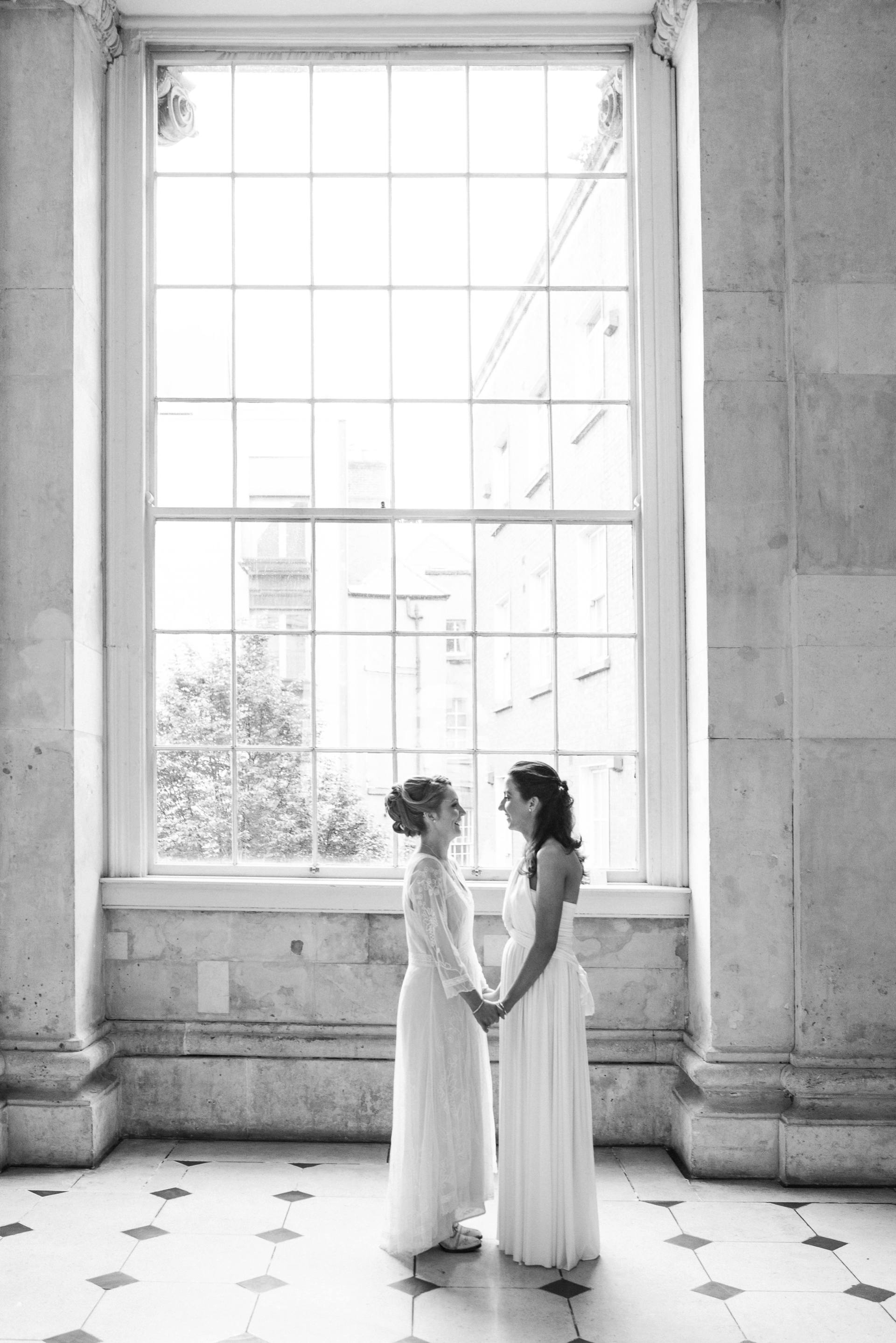Two brides holding hands in Dublin City Hall